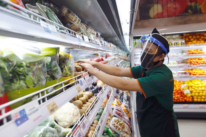 FILE PHOTO: A worker wearing a face shield and a protective face mask checks the vegetables at a Food Hall Supermarket amid the outbreak of the coronavirus disease (COVID-19), in Jakarta