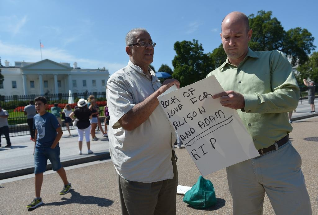 An activist holds a card for a passer-by to sign for a Virginia TV reporter and cameraman in front of the White House on August 27, 2015 in Washington, DC (AFP Photo/Mandel Ngan)
