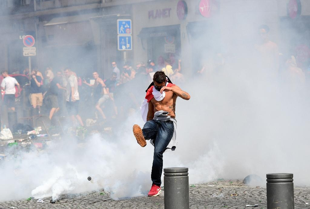 An England fan kicks away a tear gas canister after tear gas was released by French police in the city of Marseille, southern France, on June 11, 2016, ahead of the Euro 2016 football match between England and Russia (AFP Photo/Leon Neal)