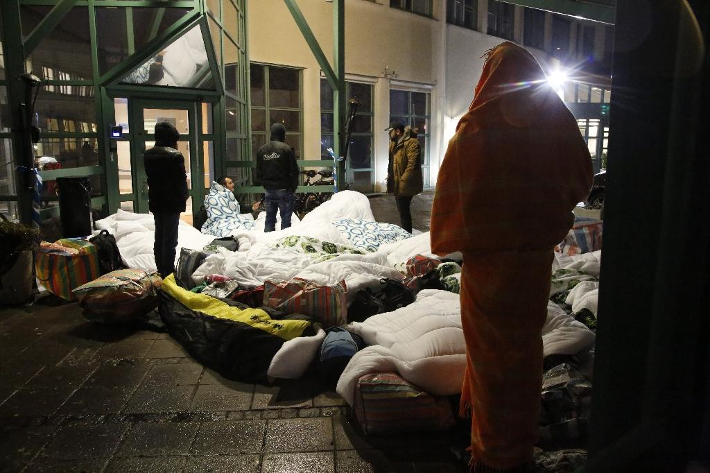 Refugees sleep outside the entrance of the Swedish Migration Agency's arrival center for asylum seekers at Jagersro in Malmo, Sweden, in November 2015 (AFP Photo/STIG-AKE JONSSON)