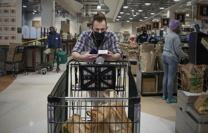 WASHINGTON,DC-APR6: Matt Gillette, a 36 year-old Instacart shopper, checks his order at a Harris Teeter in Washington, DC, April 6, 2020. For the past two years he's been part of the gig economy, driving for Lyft, doing handiwork on TaskRabbit. The work was so unstable he's been on the verge of homelessness, crashing with some friends and asking others to take in his beloved dog, a lab mix named Nitro.  For years there has been talk of a divided America, of an economy that's highly beneficial to some and detrimental to others. The wrath of a highly contagious, sometimes lethal virus has shown us where, precisely, it stands: at the front door. On one side are people who have the luxury of staying safely at home, working -- or not -- and ordering whatever they want to be delivered. On the other side are those doing the delivering. (Photo by Evelyn Hockstein/For The Washington Post via Getty Images)