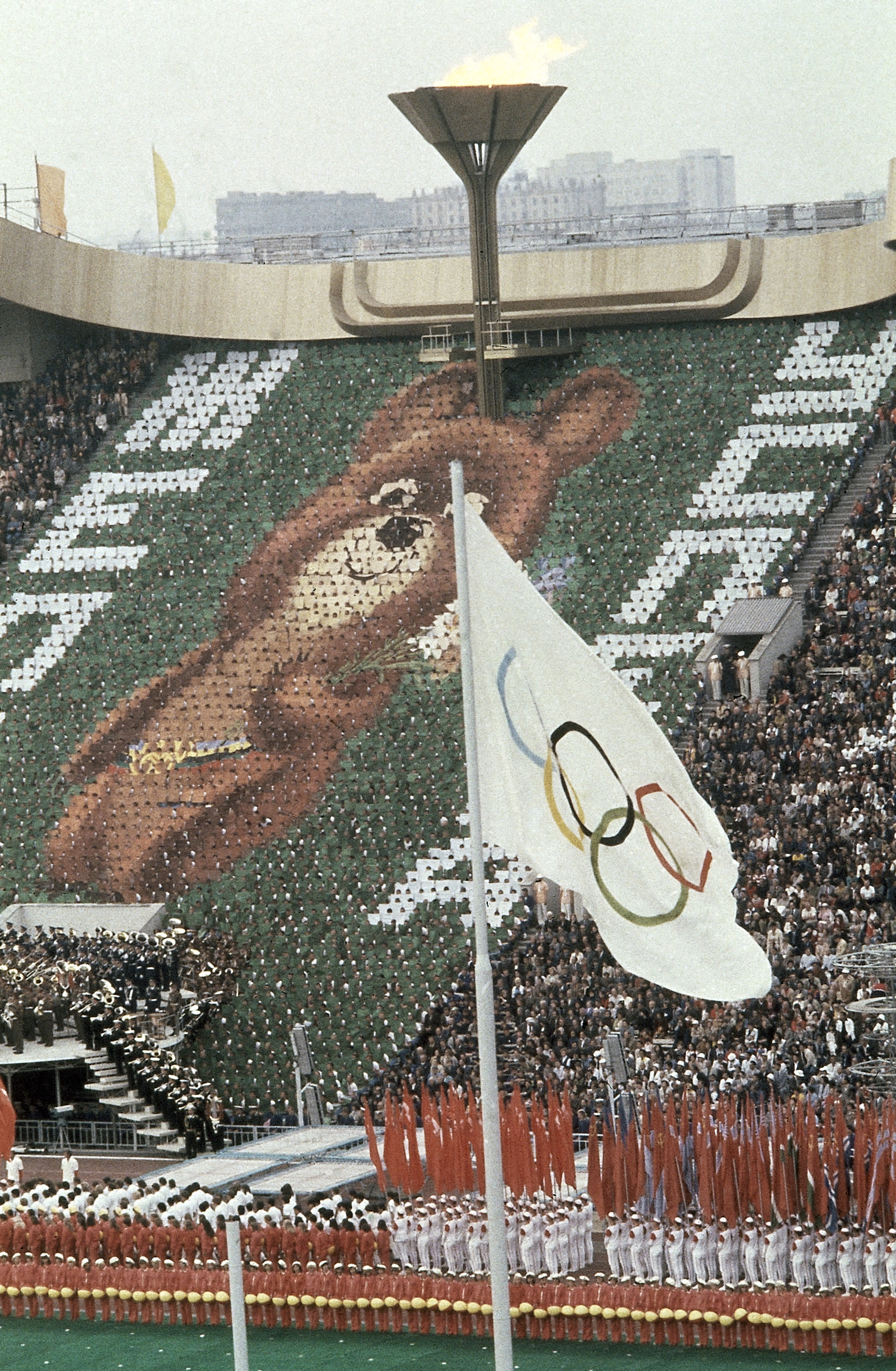 FILE - In this July 19, 1980, file photo, members of the crowd hold up 3,500 cards to create an image of Misha the Bear Cup, the mascot of the Moscow Olympic Games at the Lenin Stadium in Russia on. Above burns the Olympic flame. (AP Photo/File)
