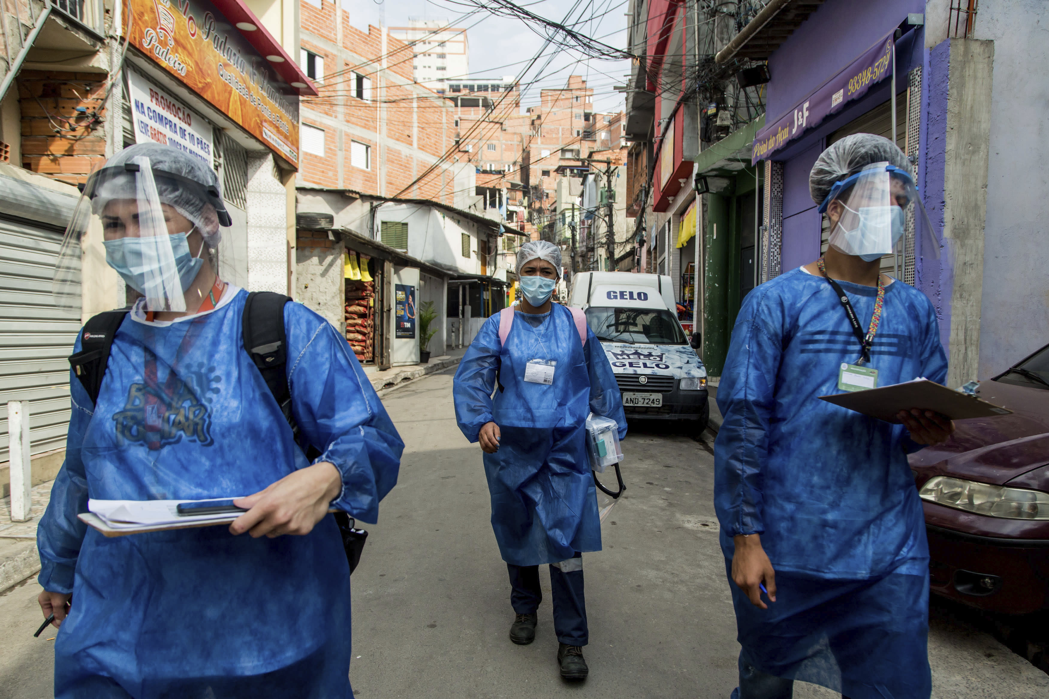 """Members of the """"Bora Testar"""" or Let's Test project, walk through the the Paraisopolis neighborhood of Sao Paulo, Brazil, Friday, Sept. 11, 2020. The project plans to test up to 600 people for COVID-19 in the low income neighborhood, and to expand to other vulnerable communities in the country, financed by crowdfunding and donations. (AP Photo/Carla Carniel)"""