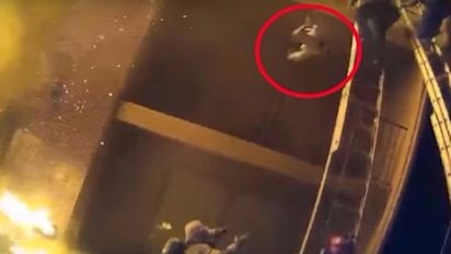 Firefighter catches child thrown from burning building