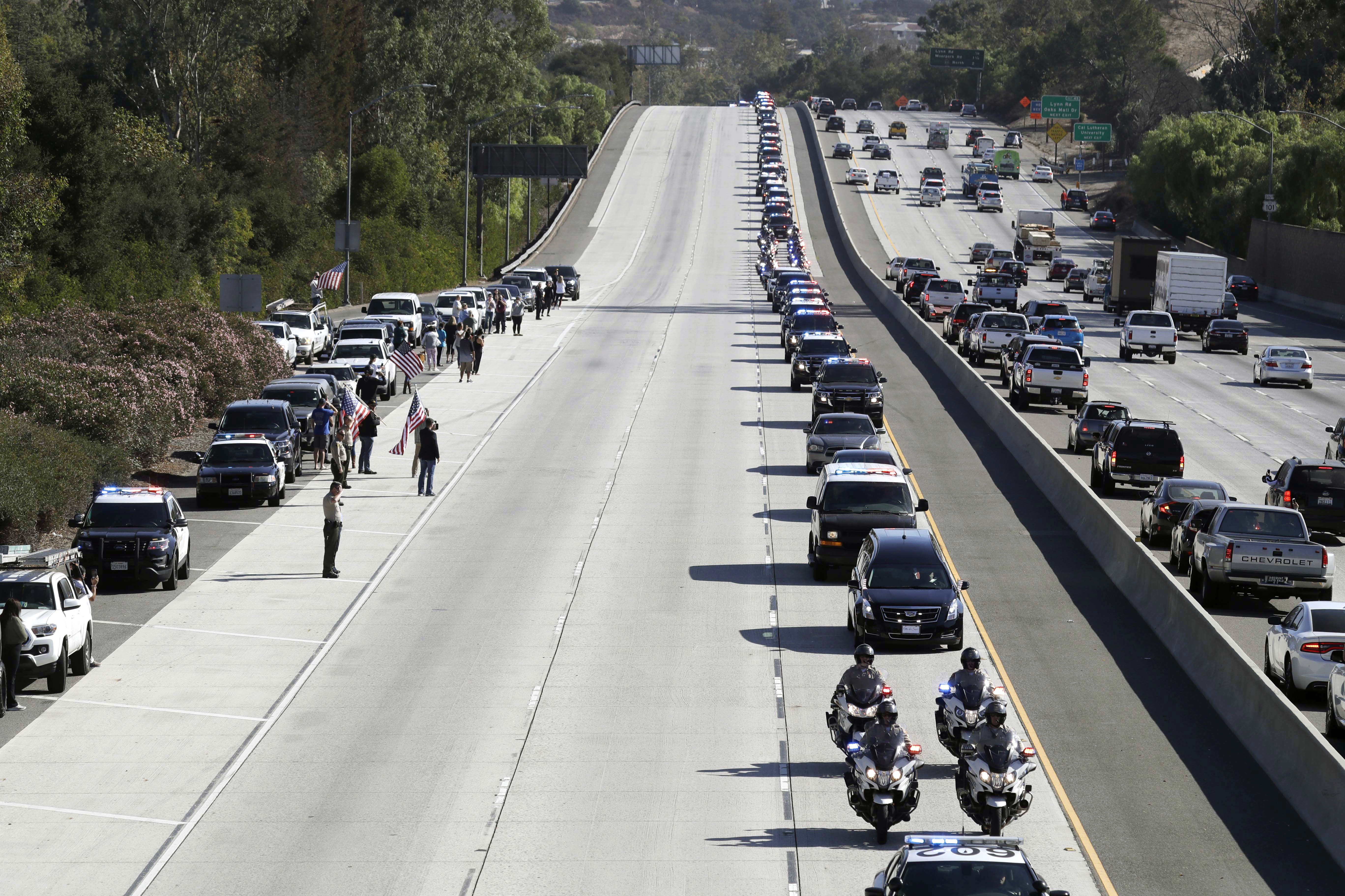 <p>A law enforcement motorcade, providing an escort for a hearse carrying the body of Ventura County Sheriff's Sgt. Ron Helus, makes its way northbound on Highway 101 Thursday, Nov. 8, 2018, in Newbury Park, Calif. Helus was fatally shot while responding to a mass shooting at a country music bar in Southern California. (Photo: Marcio Jose Sanchez/AP) </p>