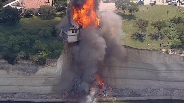 Demolition crews burn luxury house dangling at edge of cliff