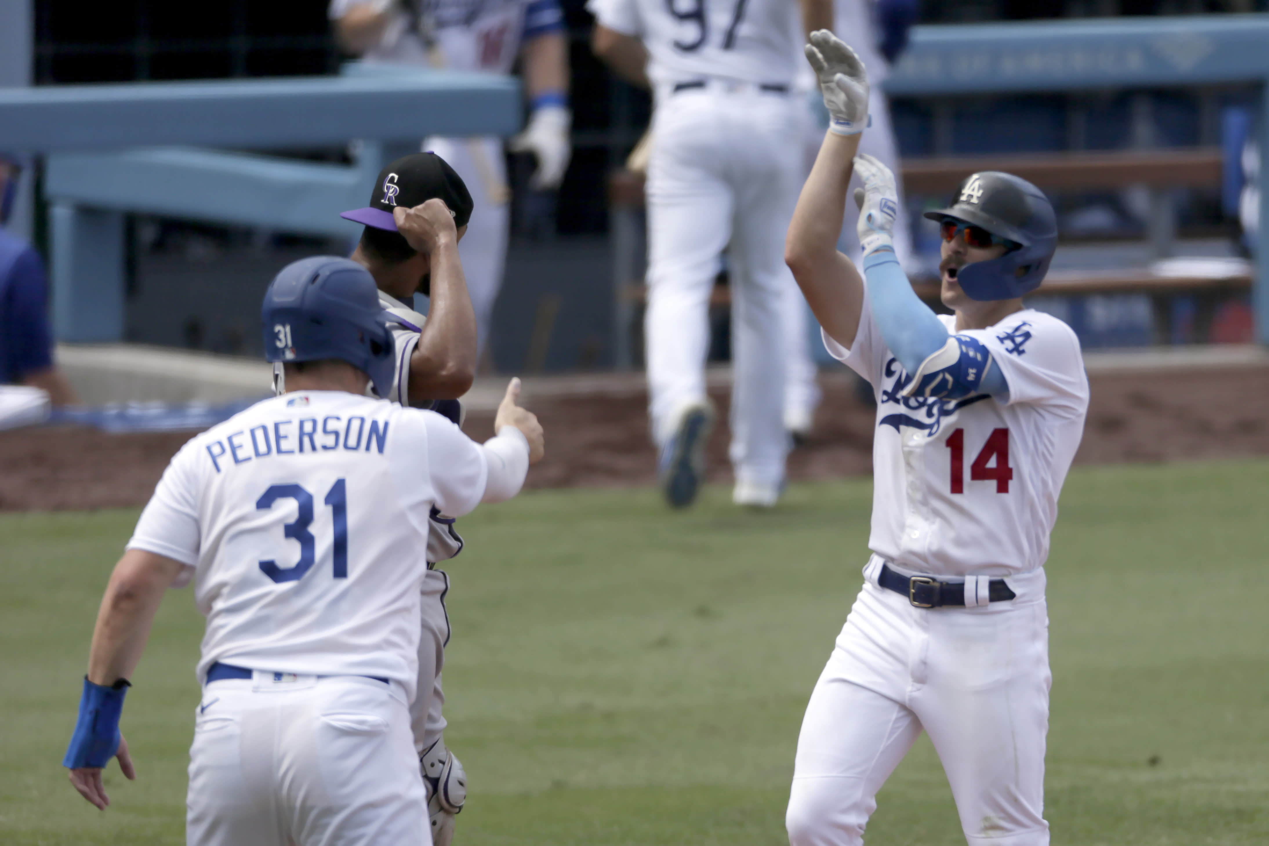 Los Angeles Dodgers' Enrique Hernandez, right, celebrates with Joc Pederson, front left, after hitting a three-run home run as Colorado Rockies catcher Elias Diaz, back left, looks away during the fourth inning of a baseball game in Los Angeles, Sunday, Aug. 23, 2020. (AP Photo/Alex Gallardo)