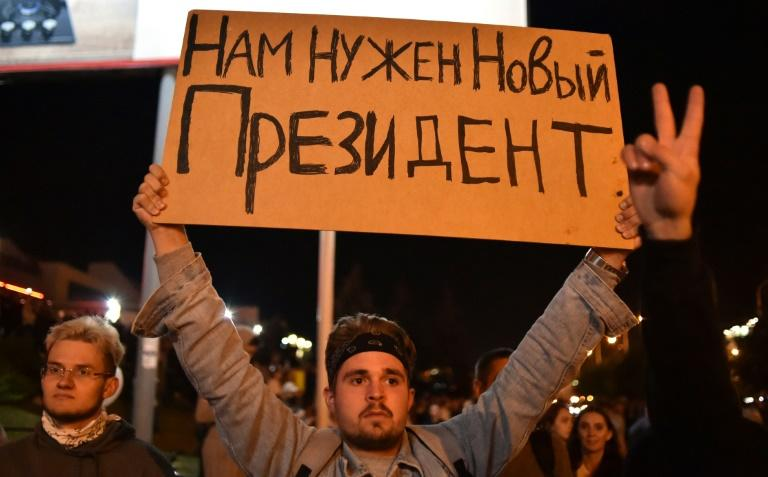 "A man holds a poster reading ""We need a new President"" during a protest rally against police violence in the wake of the disputed re-election of strongman Alexander Lukashenko"