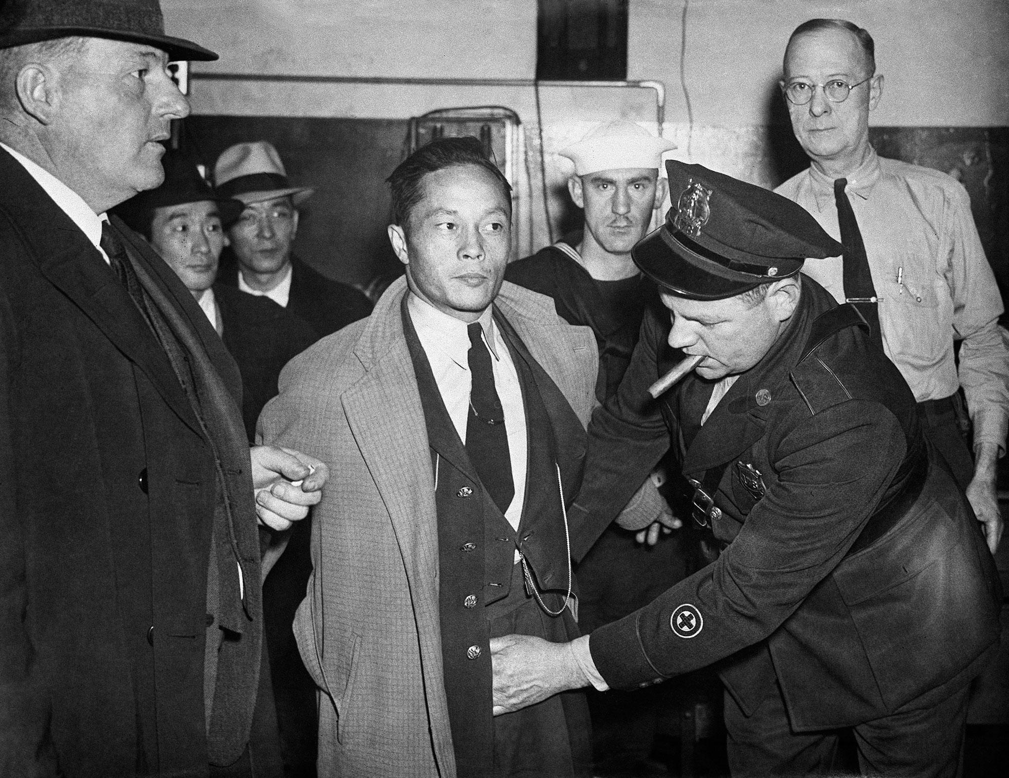 <p>A Japanese man under arrest in the roundup at Norfolk, Virginia, Dec. 7, 1941, after Japan's declaration of war on the U.S., is searched by a policeman. (AP Photo) </p>