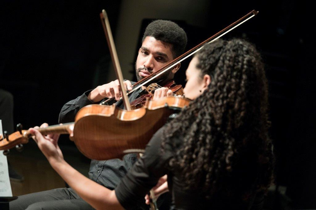 José Luis Rubio Reyes (L) casts a glance at Adriana Déborah Rodríguez Laza as members of the Cuban American Youth Orchestra perform prior to a concert by the Minnesota Orchestra in Minneapolis, Minneapolis on November 3, 2017 (AFP Photo/Courtney PERRY)