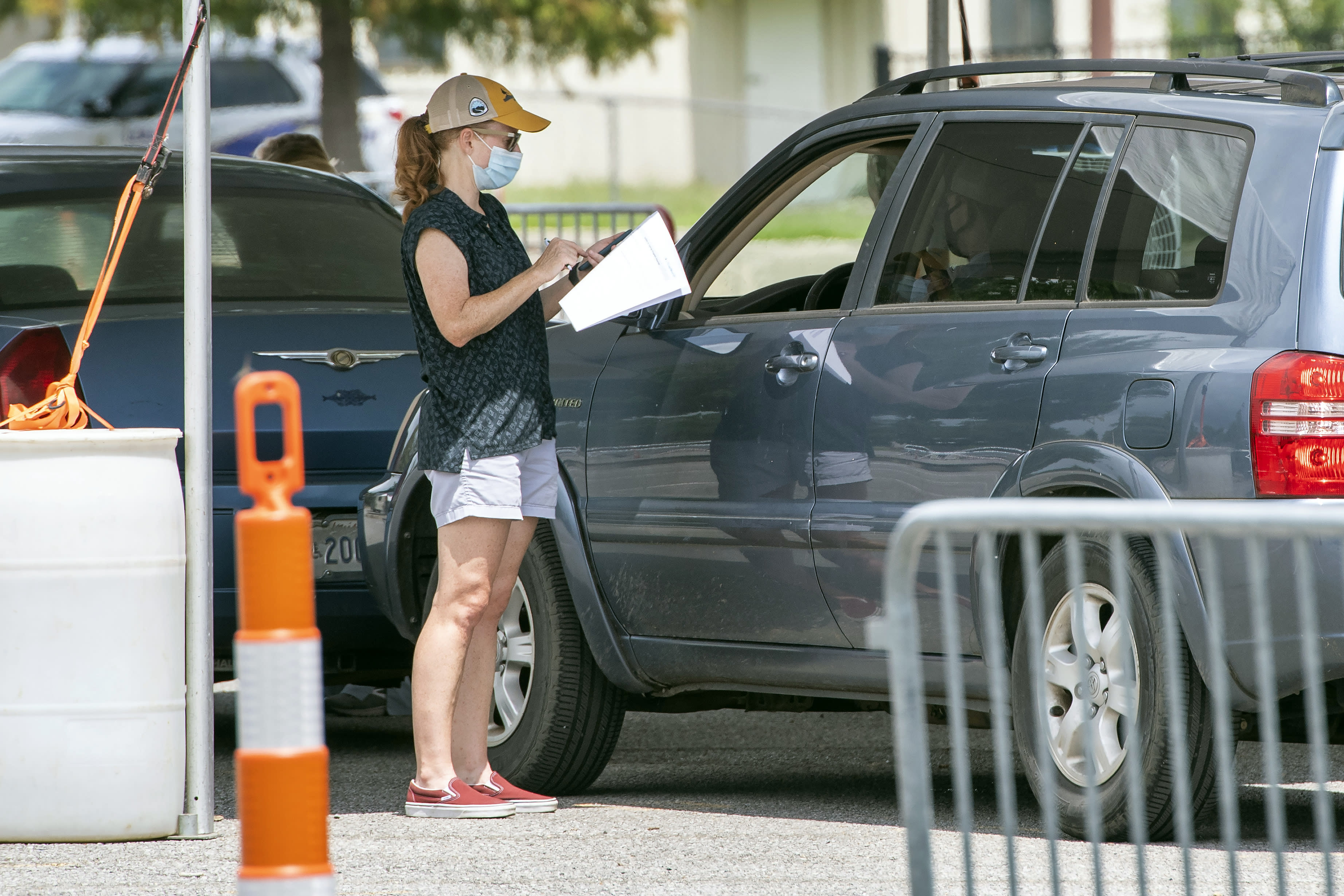 People line up at the Covid-19 testing site at LSU's Alex Box Stadium parking lot, Tuesday July 7, 2020, in Baton Rouge, La. (Bill Feig/The Advocate via AP)