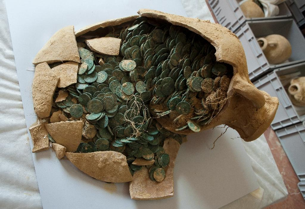 A Roman era amphora filled with bronze coins is displayed at the archaeological museum in Sevilla on April 28, 2016 following their discovery during development works for pipelines in Seville, Spain