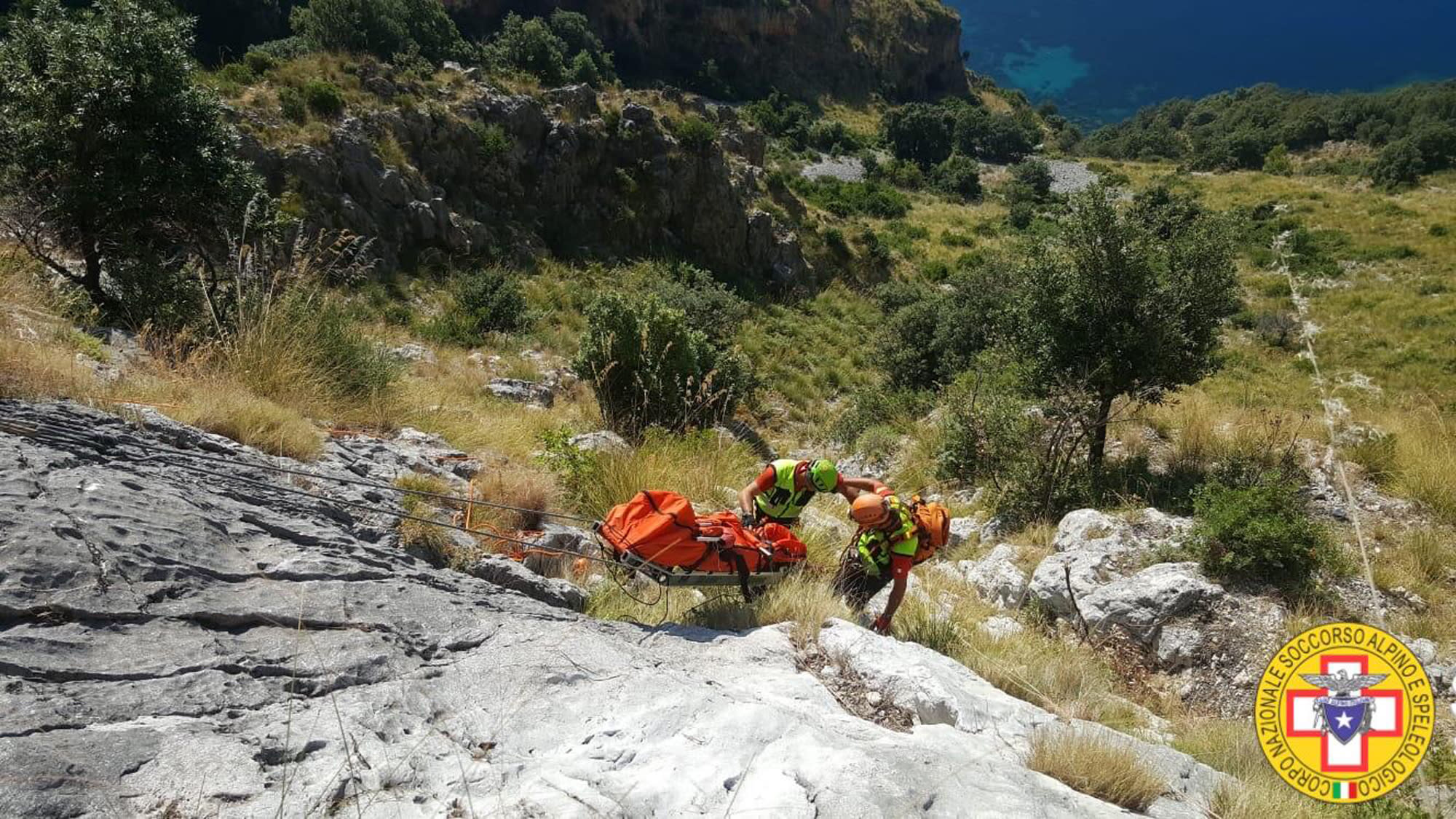 Members of the Italian mountain rescue team search for a French hiker in the Cilento region, Southern Italy, Monday, Aug. 19, 2019. Italian mountain rescue squads have recovered the body of a French hiker who fell into a ravine and broke his leg. Nine days of search ended Sunday when alpine rescue spotted Simon Gautier's backpack and then his body in a ravine in the Cilento region of Southern Italy. Crews were able to recover the body Monday. (Corpo Nazionale Soccorso Alpino e Speleologico via AP)