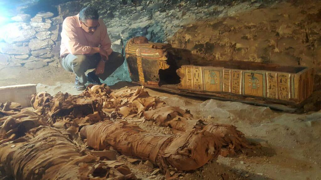An Egyptian archaeologist inspects three mummies uncovered in an ancient tomb in the Draa Abul Naga necropolis in Luxor in a handout picture released by the Egyptian antiquities ministry on September 9, 2017 (AFP Photo/Handout)