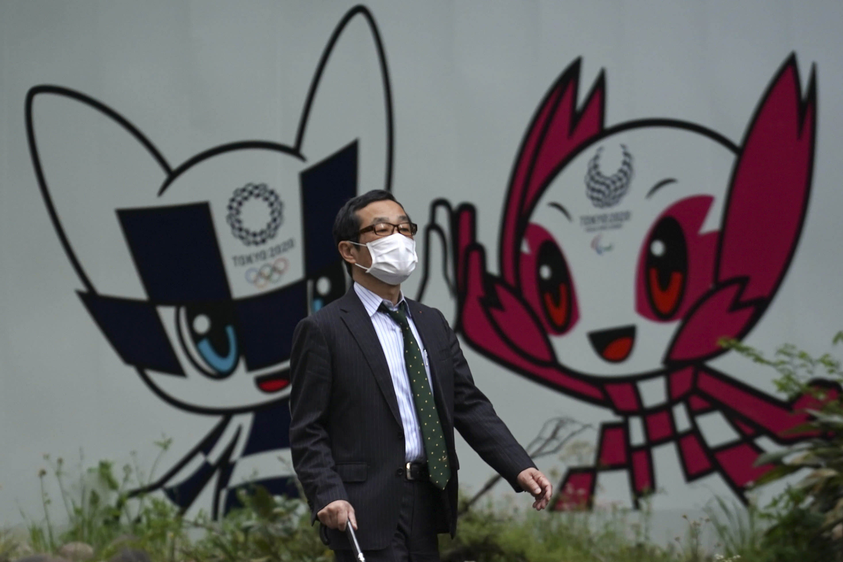 FILE - In this April 28, 2020, file photo, a man with a face mask against the spread of the new coronavirus walks in front of Miraitowa and Someity, mascots for the Tokyo 2020 Olympics and Paralympics at a park in Tokyo. The postponed Tokyo Olympics have again reached the one-year-to-go mark. But the celebration is small this time with more questions than answers about how the Olympics can happen in the middle of a pandemic. That was before COVID-19 postponed the Olympics and pushed back the opening to July 23, 2021. (AP Photo/Eugene Hoshiko, File)