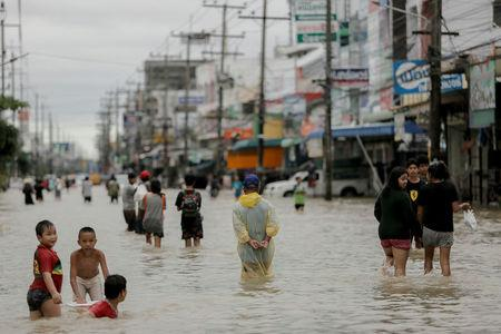 REFILE - CORRECTING GRAMMARPeople walk in a flooded street at Muang district in Nakhon Si Thammarat Province, southern Thailand, January 6, 2017. REUTERS/Wirittipon Withandetsit FOR EDITORIAL USE ONLY. NO RESALES. NO ARCHIVES