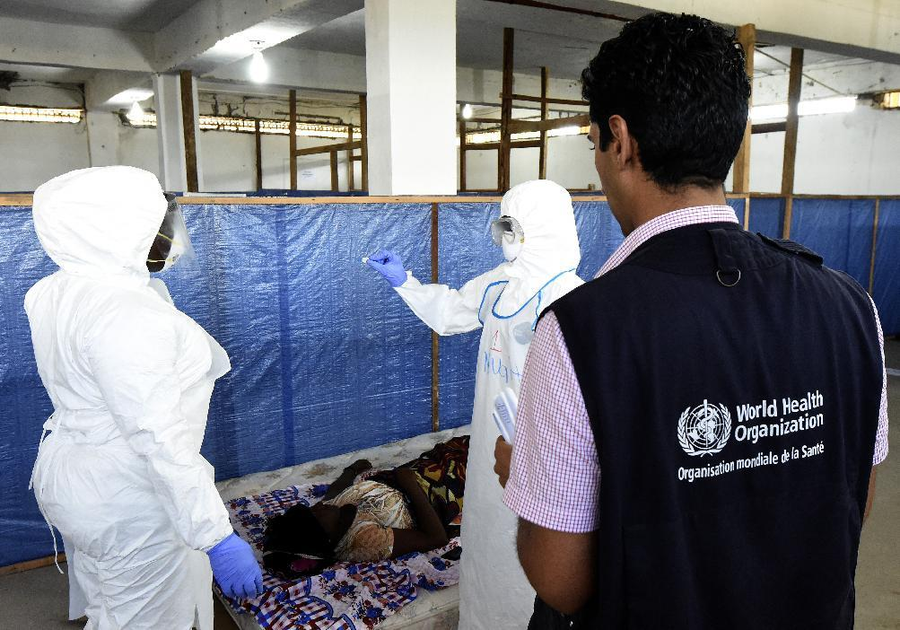 Health workers check on a person acting as a patient at a World Health Organization health center during a training session for the Ebola virus in the Liberian capital Monrovia, on October 3, 2014 (AFP Photo/Pascal Guyot)