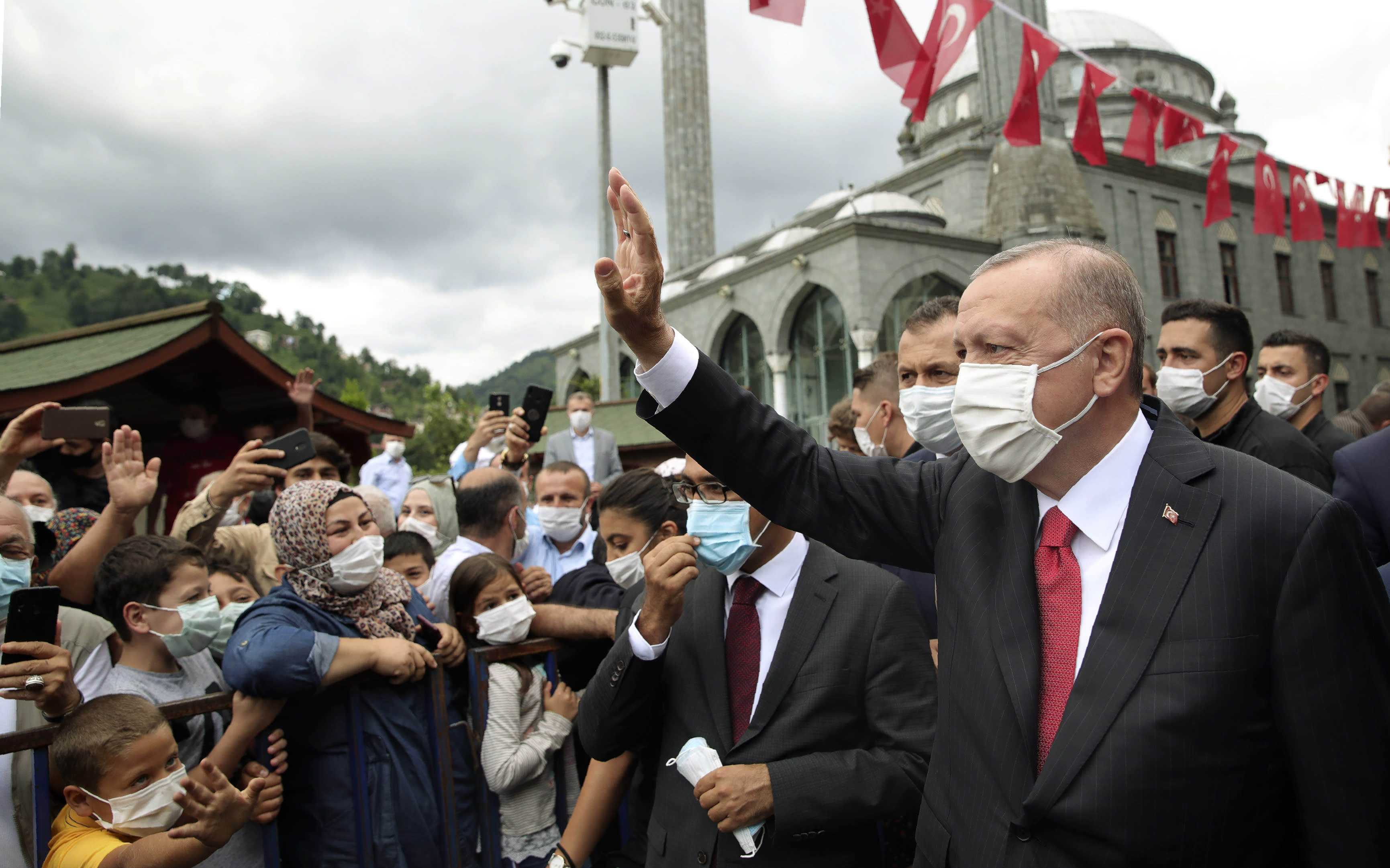 Turkey's President Recep Tayyip Erdogan wearing a face mask to protect against the spread of coronavirus, waves toward his supporters in Black Sea city of Rize, Turkey, Saturday, Aug. 15, 2020. Turkey's health minister says the number of new COVID-19 infections Saturday has hit its highest in 45 days and announced 1,256 new cases.(Turkish Presidency via AP, Pool)