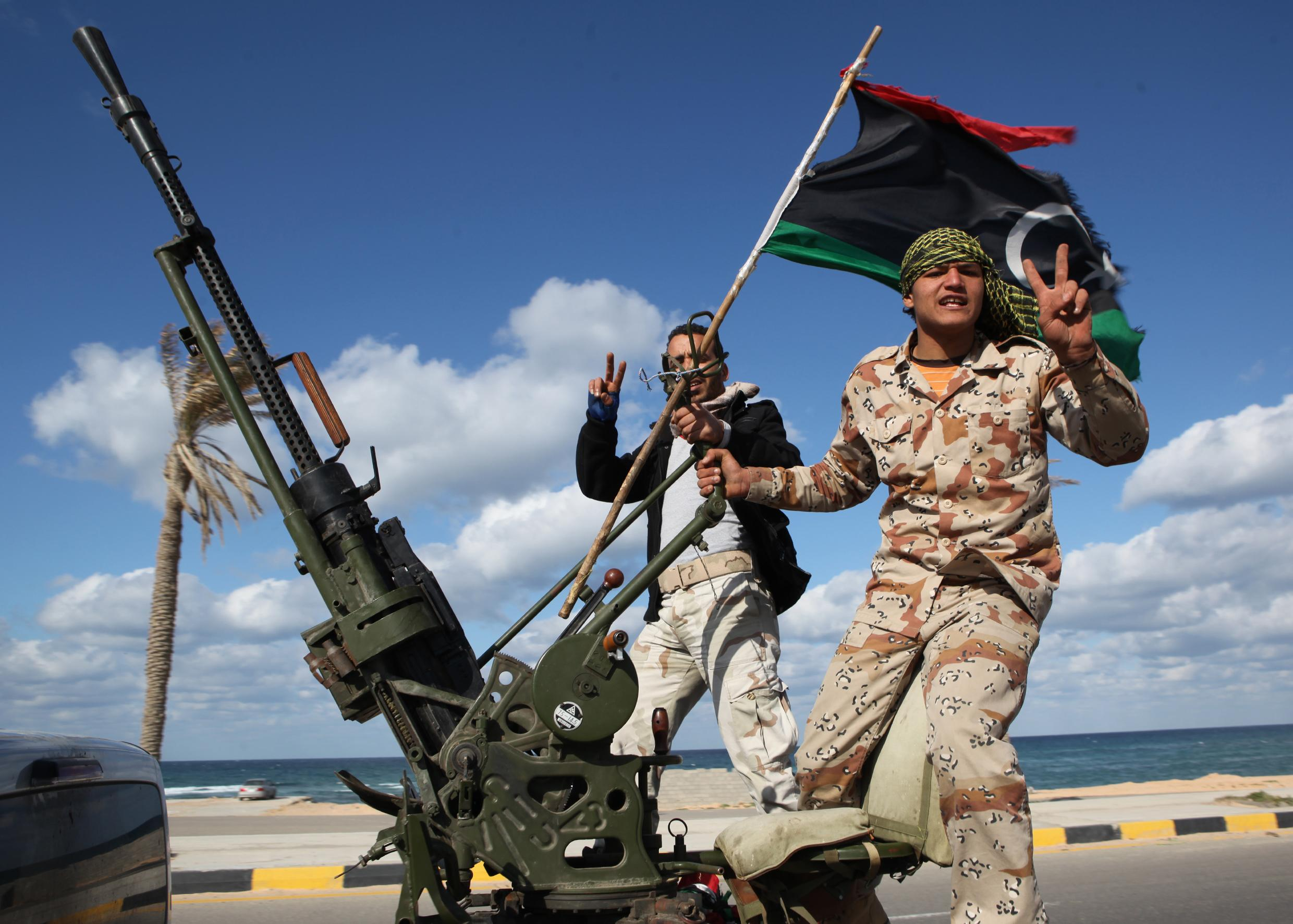 FILE - In this Tuesday Feb. 14, 2012 file photo, Libyan militias from towns throughout the country's west parade through Tripoli, Libya. At the heart of the Libyan capital, the open-air Fish Market was once where residents went to buy everything from meat and seafood to clothes and pets. Now it's Tripoli's biggest arms market, with tables displaying pistols and assault rifles. Ask a vendor, and he can pull out bigger machine guns to sell for thousands of dollars. (AP Photo/Abdel Magid Al Fergany, File)