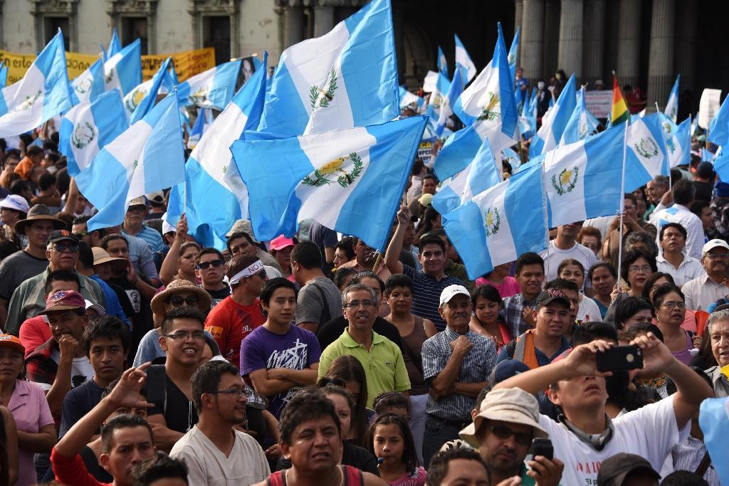 People hold national flags as they take part in a demonstration to demand that Guatemalan President Otto Perez resign over a corruption scandal, in Guatemala City on August 22, 2015 (AFP Photo/Johan Ordonez)