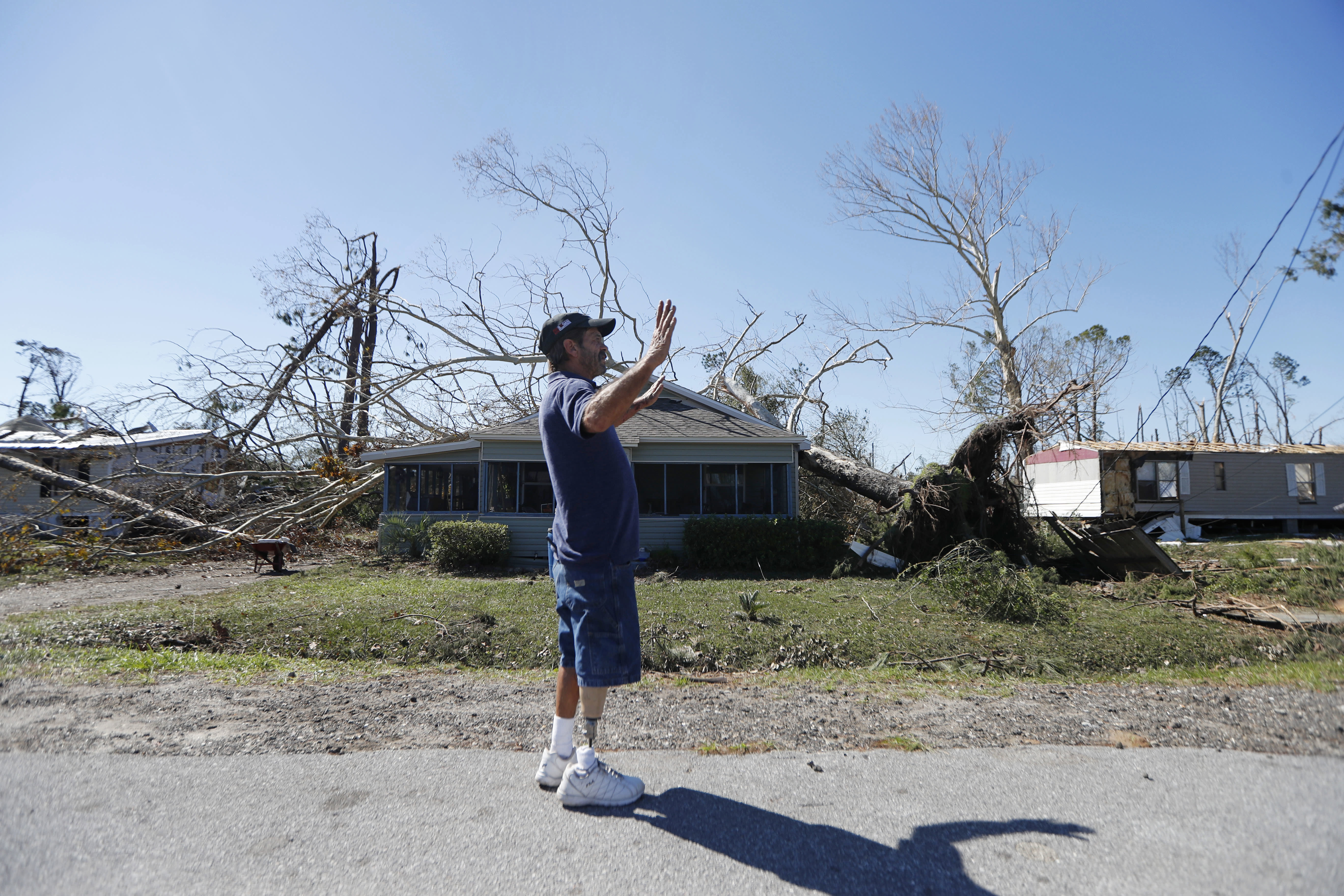 In this Oct. 13, 2018 photo, Clinton Moseley who lives with his mother, stands in front of her home after a tree fell on the home during Hurricane Michael, in Panama City, Fla. The house has been in his family for a century. Water gushed in, but he said they're staying. (AP Photo/Gerald Herbert)