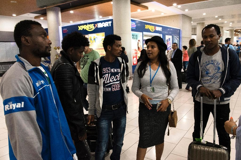 A volunteer (2R) talks to four African refugees after they arrived at Larnaca International airport from Italy on May 17, 2016 as part of an EU relocation programme