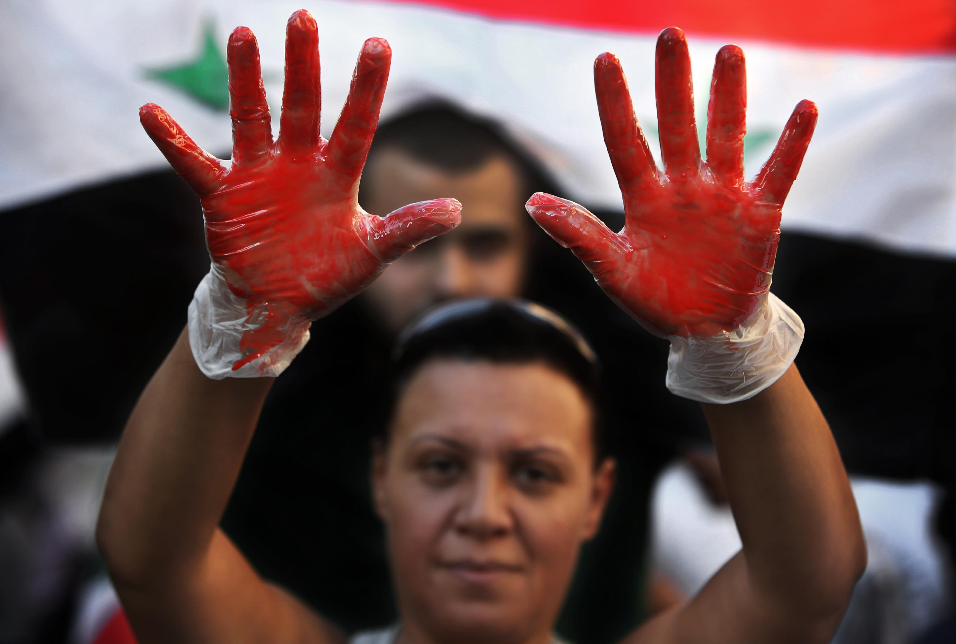 A Lebanese pro-Syrian regime supporter, with her hands painted in red to symbolize blood, attends a demonstration against a possible military strike in Syria, near the U.S. Embassy in Awkar, east of Beirut, Lebanon, Friday, Sept. 6, 2013. The prospect of a U.S.-led strike against Syria has raised concerns of potential retaliation from the Assad regime or its allies. The State Department ordered nonessential U.S. diplomats to leave Lebanon over security concerns and urged private American citizens to depart as well. (AP Photo/Hussein Malla)