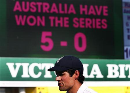 England's captain Alastair Cook reacts as he walks off the field past the board displaying the result of their fifth Ashes cricket test against Australia at the Sydney Cricket Ground