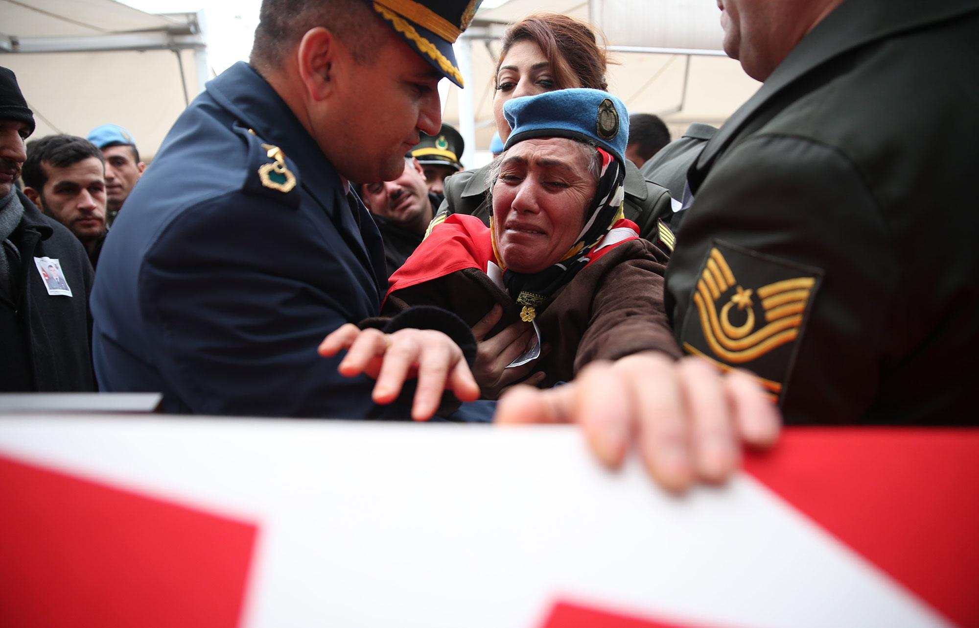 <p>Fadime Demir, mother of the Turkish soldier Ferhat Demir martyred in Operation Euphrates Shield in Syria, wearing her son's beret cries over the Turkish flag-draped coffin during the funeral ceremony in Bursa, Turkey on Dec. 23, 2016. Operation Euphrates Shield began in late August to improve security, support coalition forces and eliminate the terror threat along Turkeys border using Free Syrian Army fighters backed by Turkish artillery and jets. (Photo: Ali Atmaca/Anadolu Agency/Getty Images) </p>