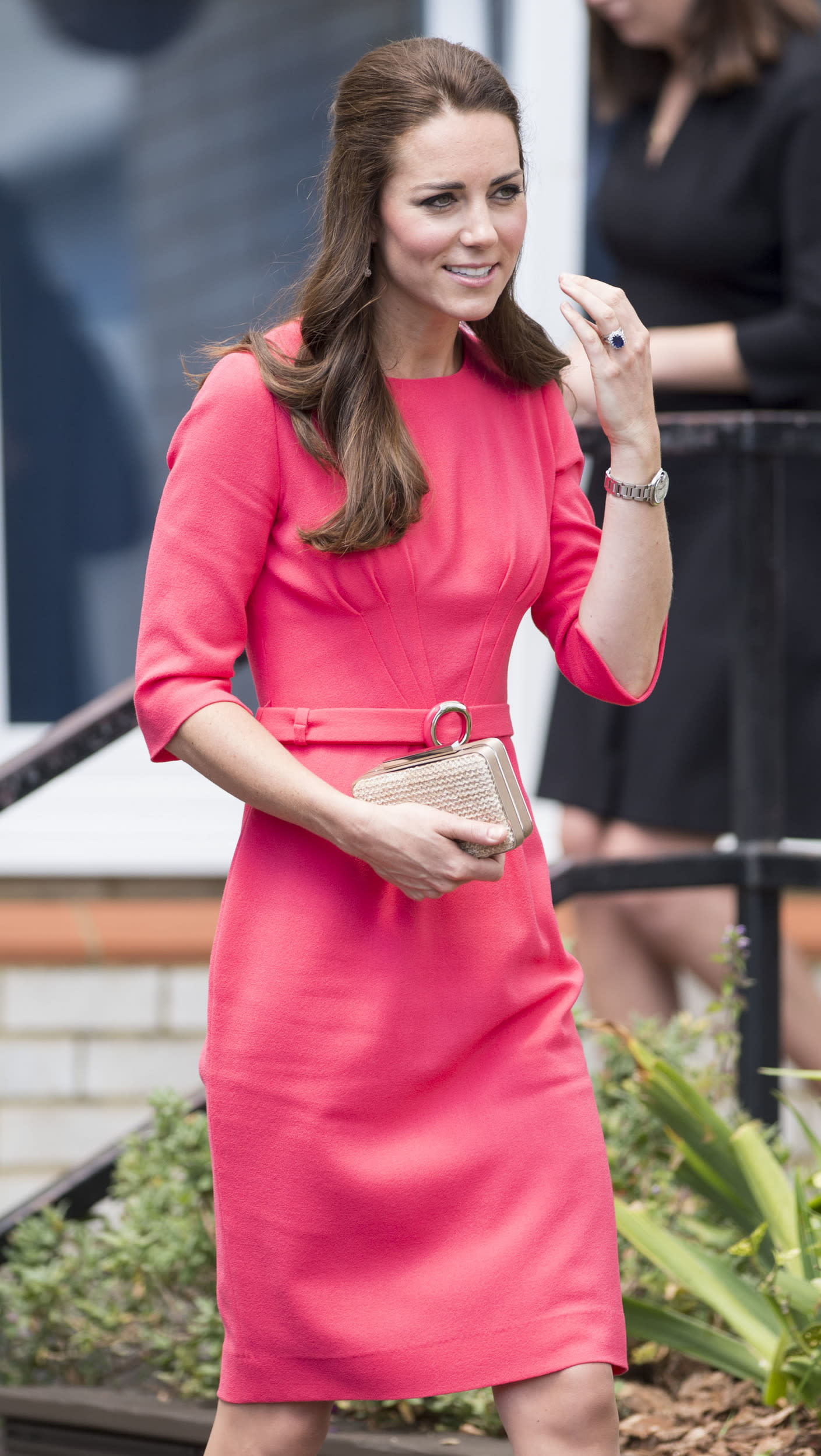 The Duchess of Cambridge visits an M-PACT Plus Counselling programme at Blessed Sacrament School on July 1st in a coral GOAT dress with cream clutch.