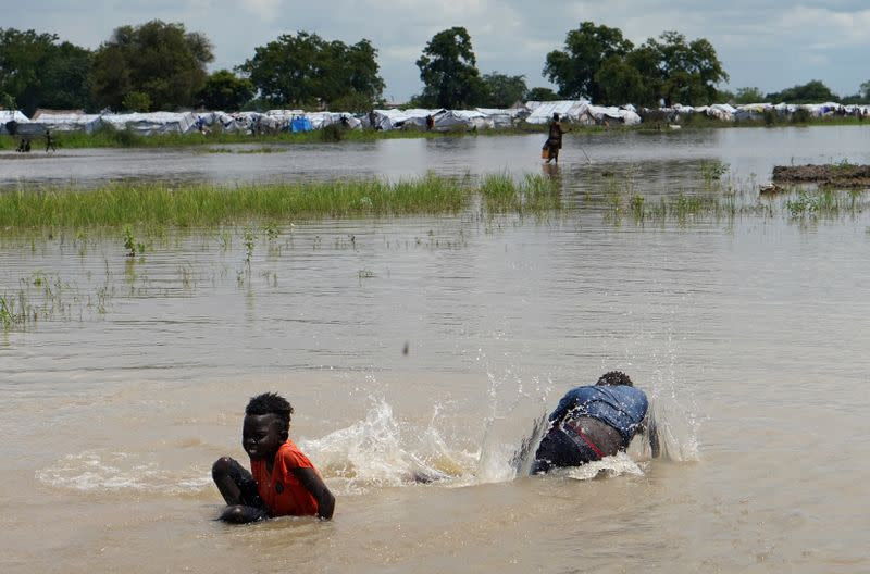 Children play in floodwaters at the airstrip after the River Nile broke the dykes in Pibor