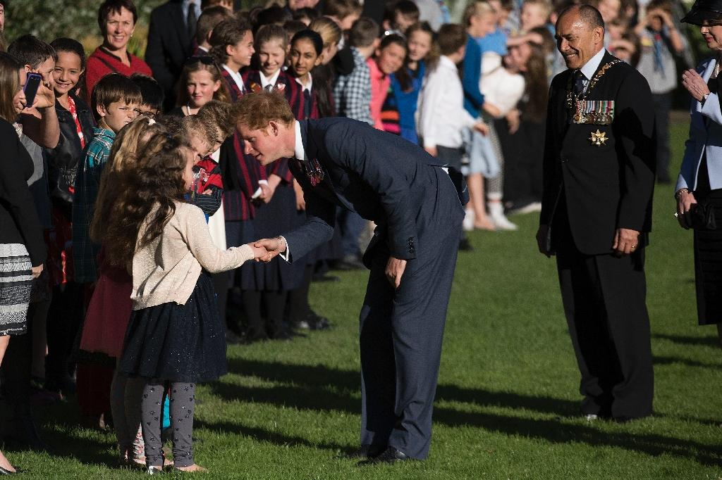 Prince Harry speaks to schoolchildren while Governor General of New Zealand Jerry Mateparae (R) looks on at a welcoming at Government House in Wellington on May 9, 2015 (AFP Photo/Marty Melville)