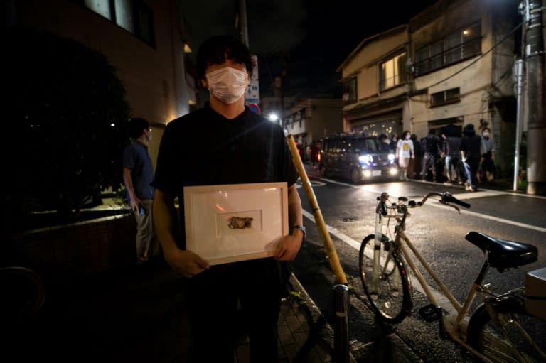 "Yusuke Hasada poses with artwork ""My Money"" created by Gabin Ito outside Same gallery (AFP Photo/Behrouz MEHRI)"