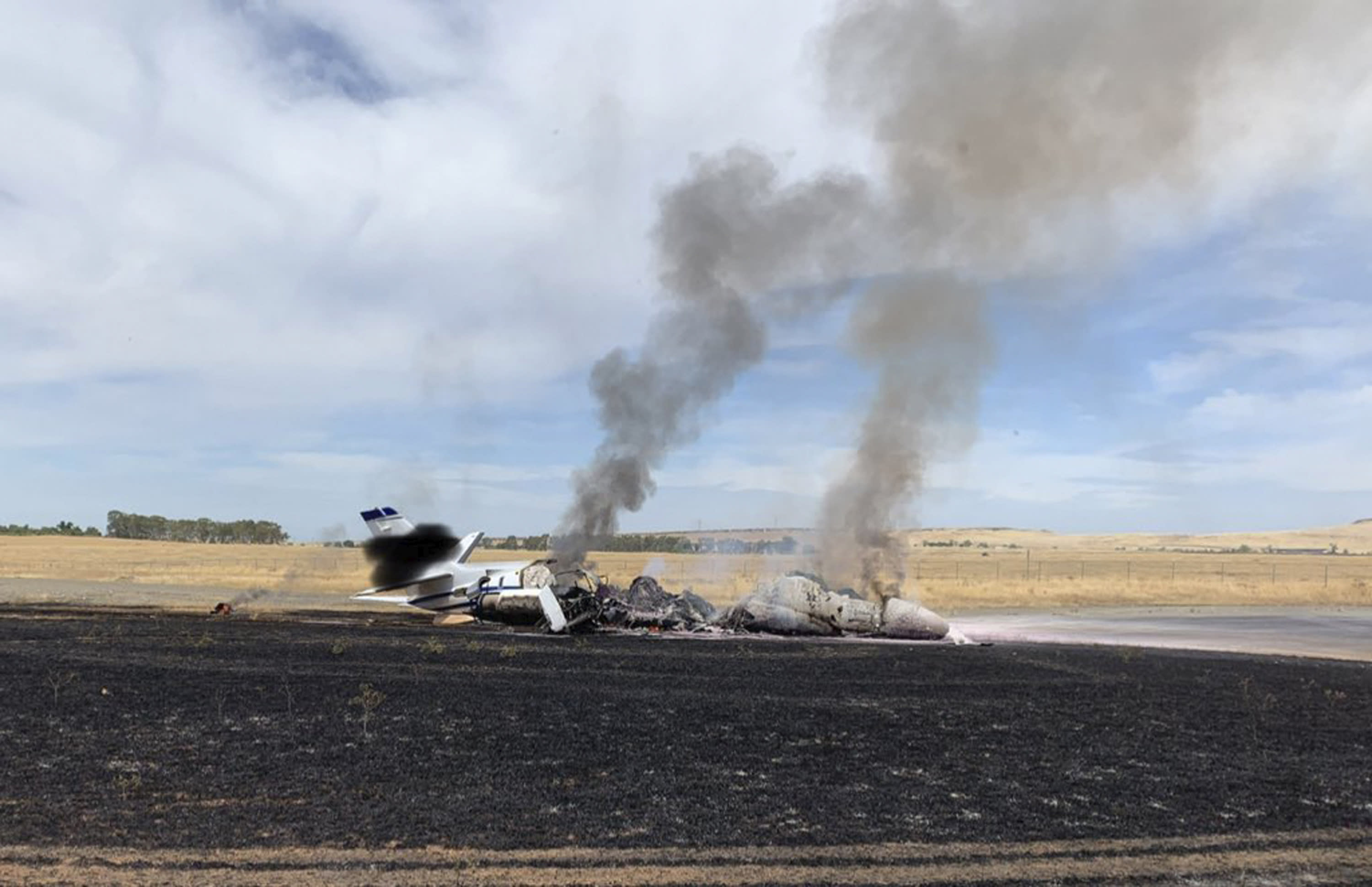 In this photo provided by the California Highway Patrol is the scene where a jet burst into flames after aborting a takeoff Wednesday, Aug. 21, 2019, in Oroville, Calif. Officials say a small jet burst into flames while trying to take off from a small Northern California airport, but all 10 people on board escaped injury. The Federal Aviation Administration says the pilot of the twin-engine Cessna Citation jet aborted its takeoff at Oroville Municipal Airport for unknown reasons shortly before noon Wednesday. The aircraft slid off the end of the runway into the grass and caught fire. The plane was flying from Oroville to Portland International Airport in Oregon. (California Highway Patrol via AP)