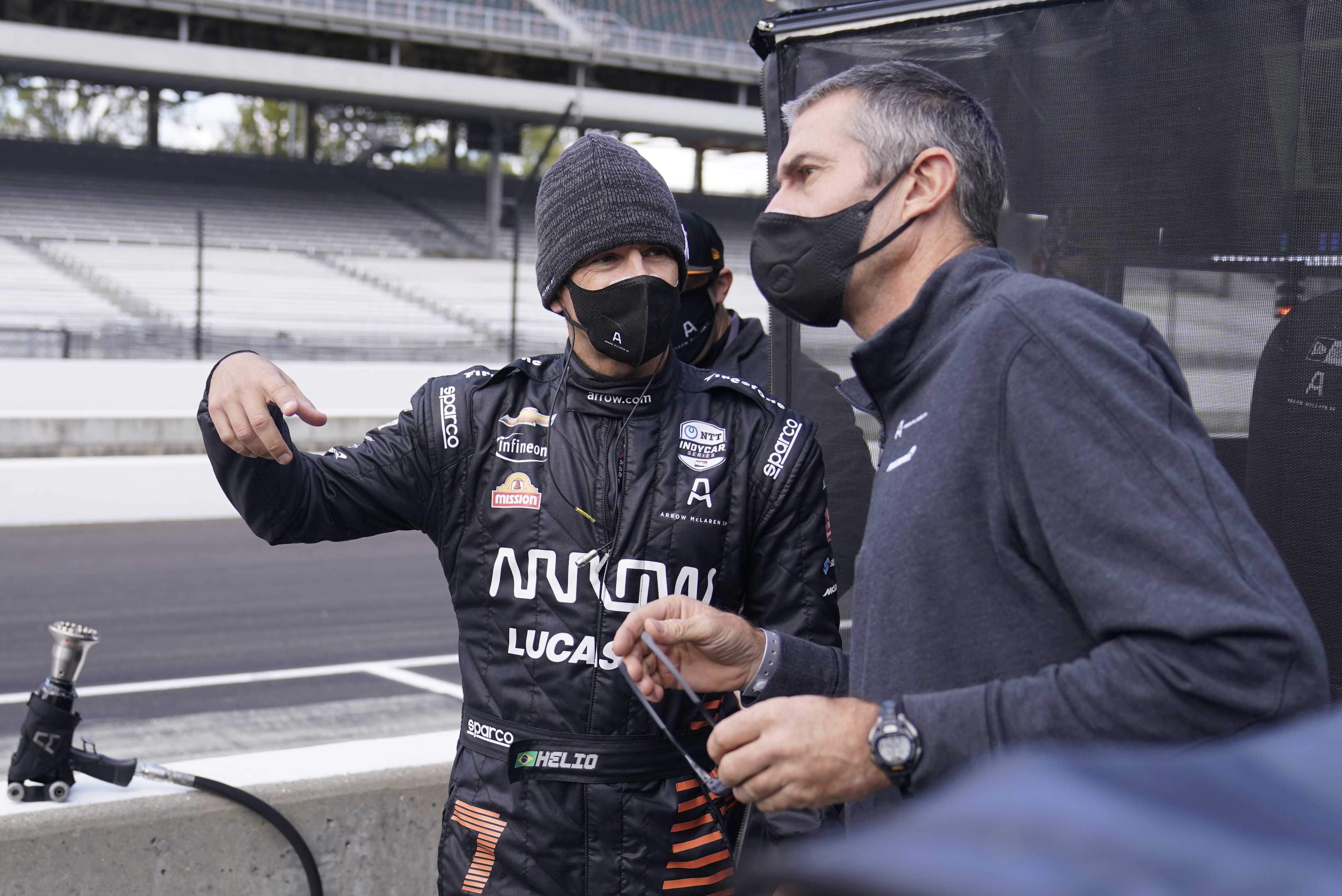 Helio Castroneves, left, of Brazil, talks with a crew member during a practice session for an IndyCar auto race at Indianapolis Motor Speedway, Thursday, Oct. 1, 2020, in Indianapolis. (AP Photo/Darron Cummings)