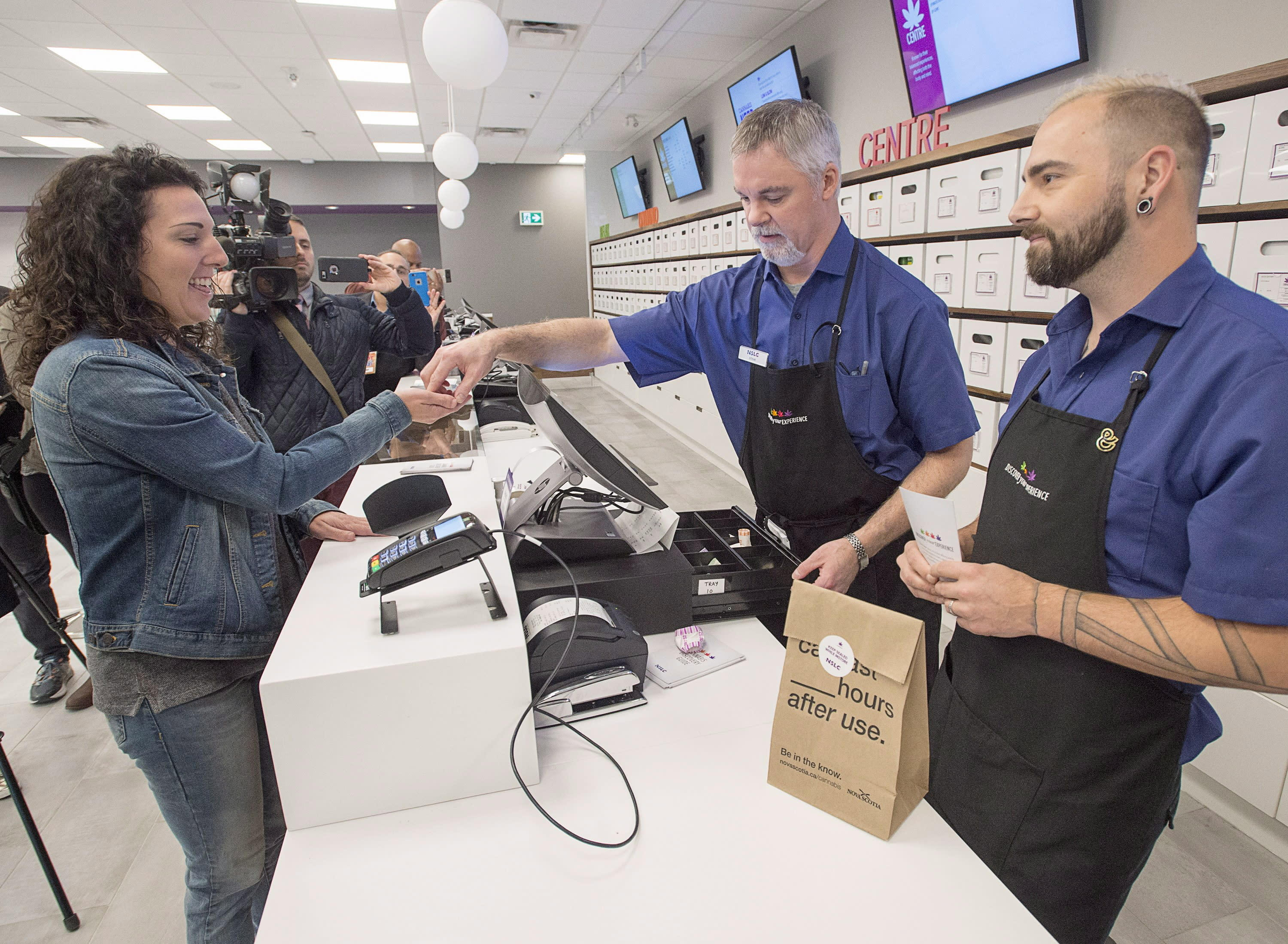 <p>Alicia Wright makes a purchase at the Nova Scotia Liquor Corporation cannabis store in Halifax on Oct. 17, 2018. Residents can make their purchases at 12 Nova Scotia Liquor Corporation stores across the province and online.<br>(Photo from Andrew Vaughan, The Canadian Press) </p>