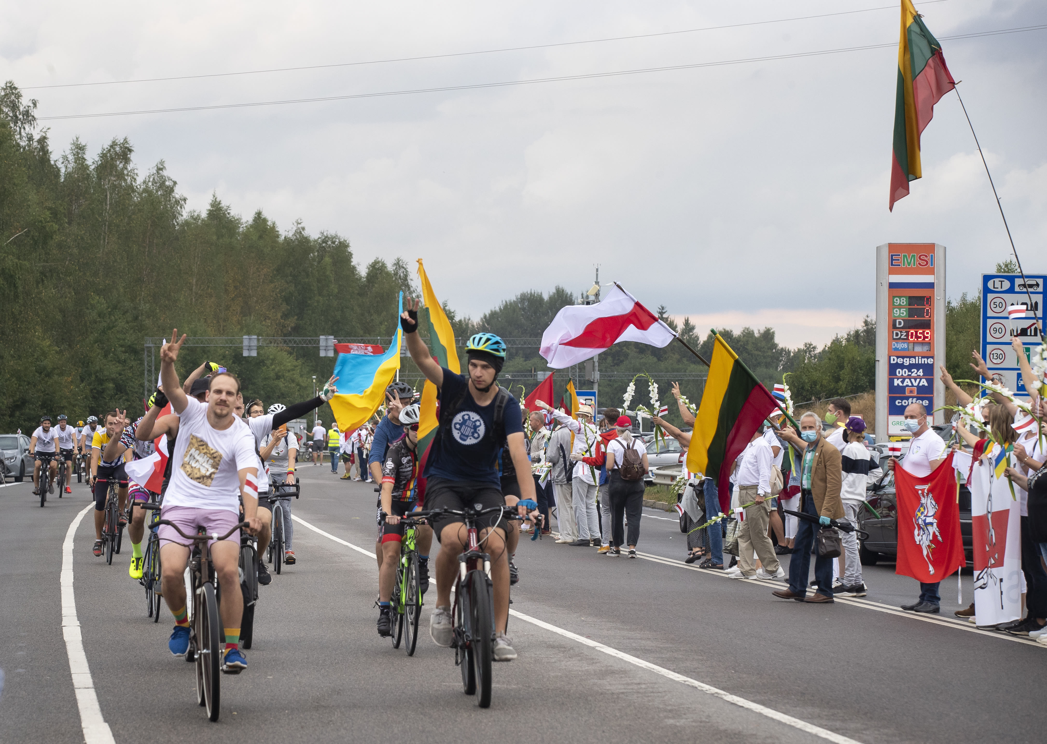 Belarusian opposition supporters ride bicycles, show victory as people create a human chain of about 50,000 strong from Vilnius to the Belarusian border during a protest near Medininkai, Lithuanian-Belarusian border crossing east of Vilnius, Lithuania, Sunday, Aug. 23, 2020. In Aug. 23, 1989, around 2 million Lithuanians, Latvians, and Estonians joined forces in a living 600 km (375 mile) long human chain Baltic Way, thus demonstrating their desire to be free. Now, Lithuania is expressing solidarity with the people of Belarus, who are fighting for freedom today. (AP Photo/Mindaugas Kulbis)