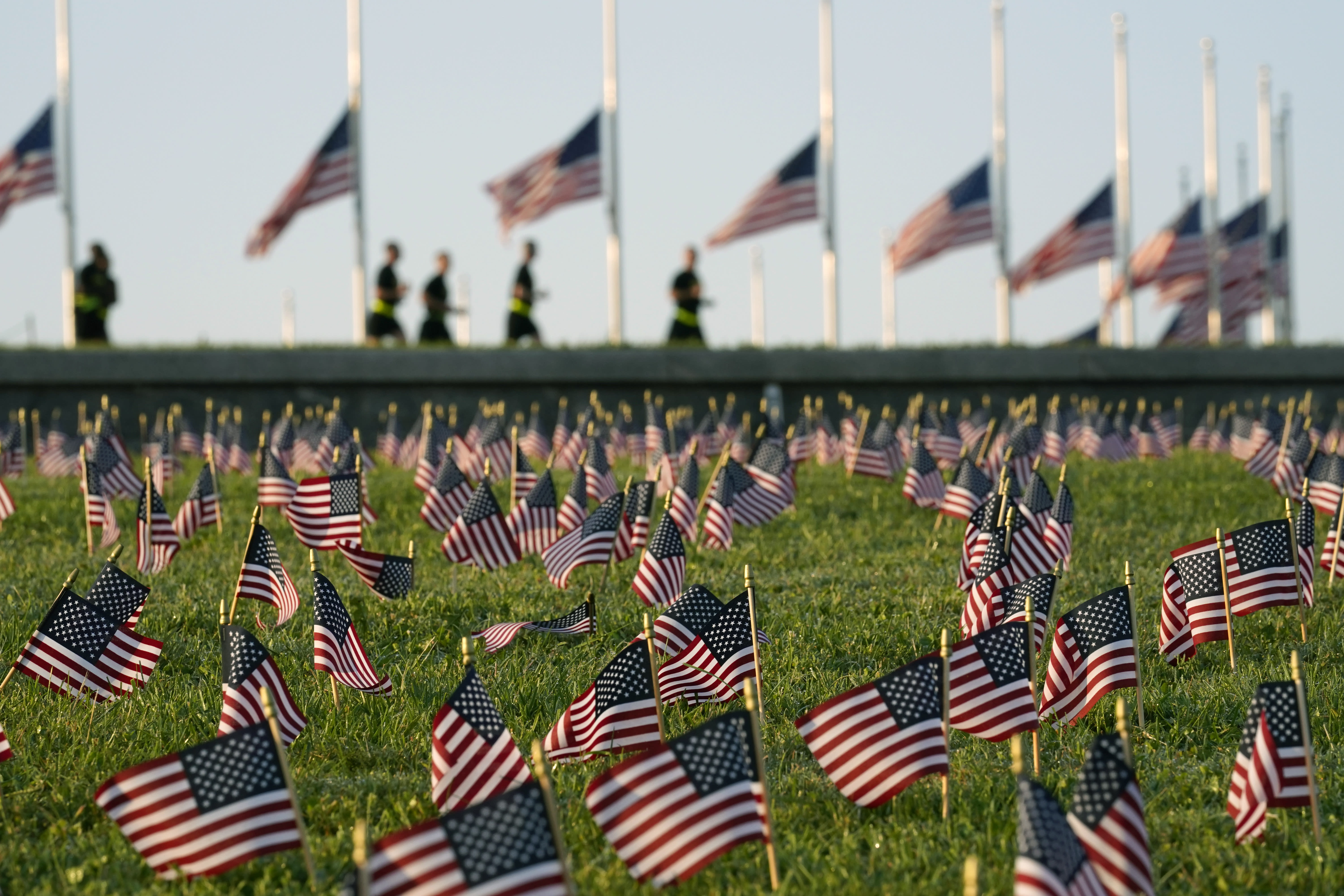 Activists from the COVID Memorial Project mark the deaths of 200,000 lives lost in the U.S. to COVID-19 after placing thousands of small American flags on the grounds of the National Mall in Washington, Tuesday, Sept. 22, 2020. (AP Photo/J. Scott Applewhite)