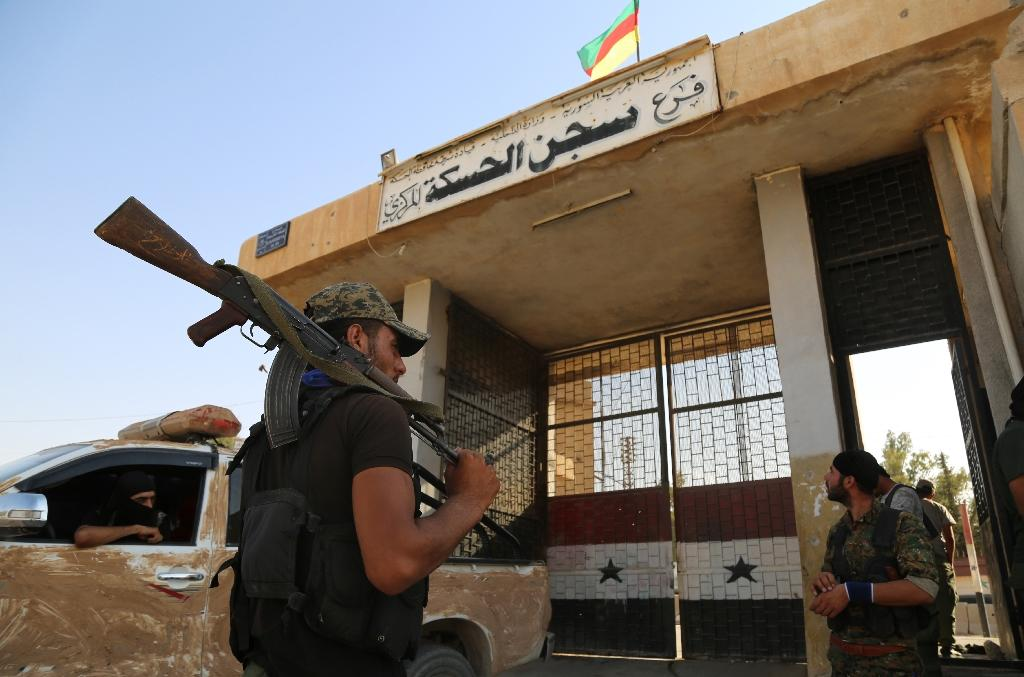 Syrian Kurdish police stand guard outside the central prison in the northeastern city of Hasakeh, one of the institutions Damascus wants back under its control