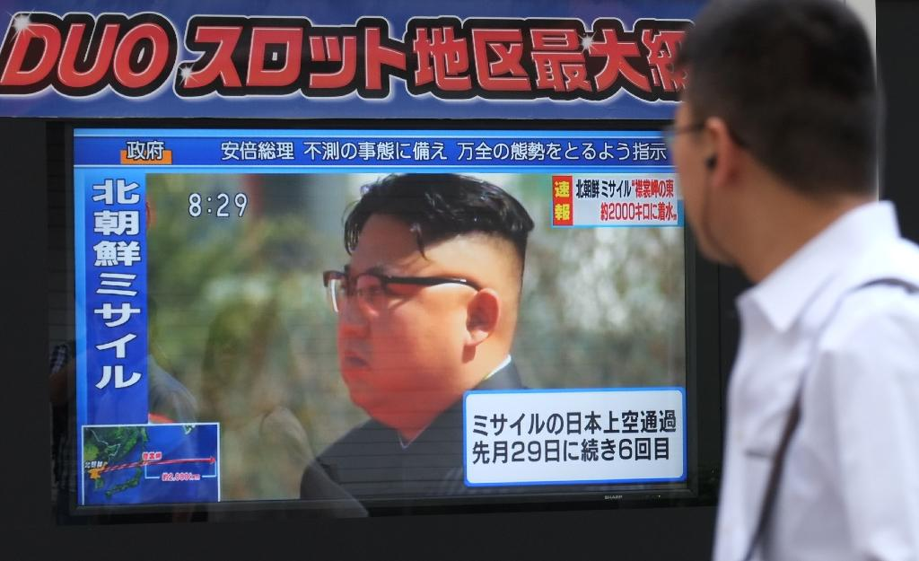 Pedestrians in Tokyo walk past a television screen broadcasting a news report showing North Korean leader Kim Jong-Un on September 15, 2017, following a North Korean missile test that passed over Japan (AFP Photo/Kazuhiro NOGI)