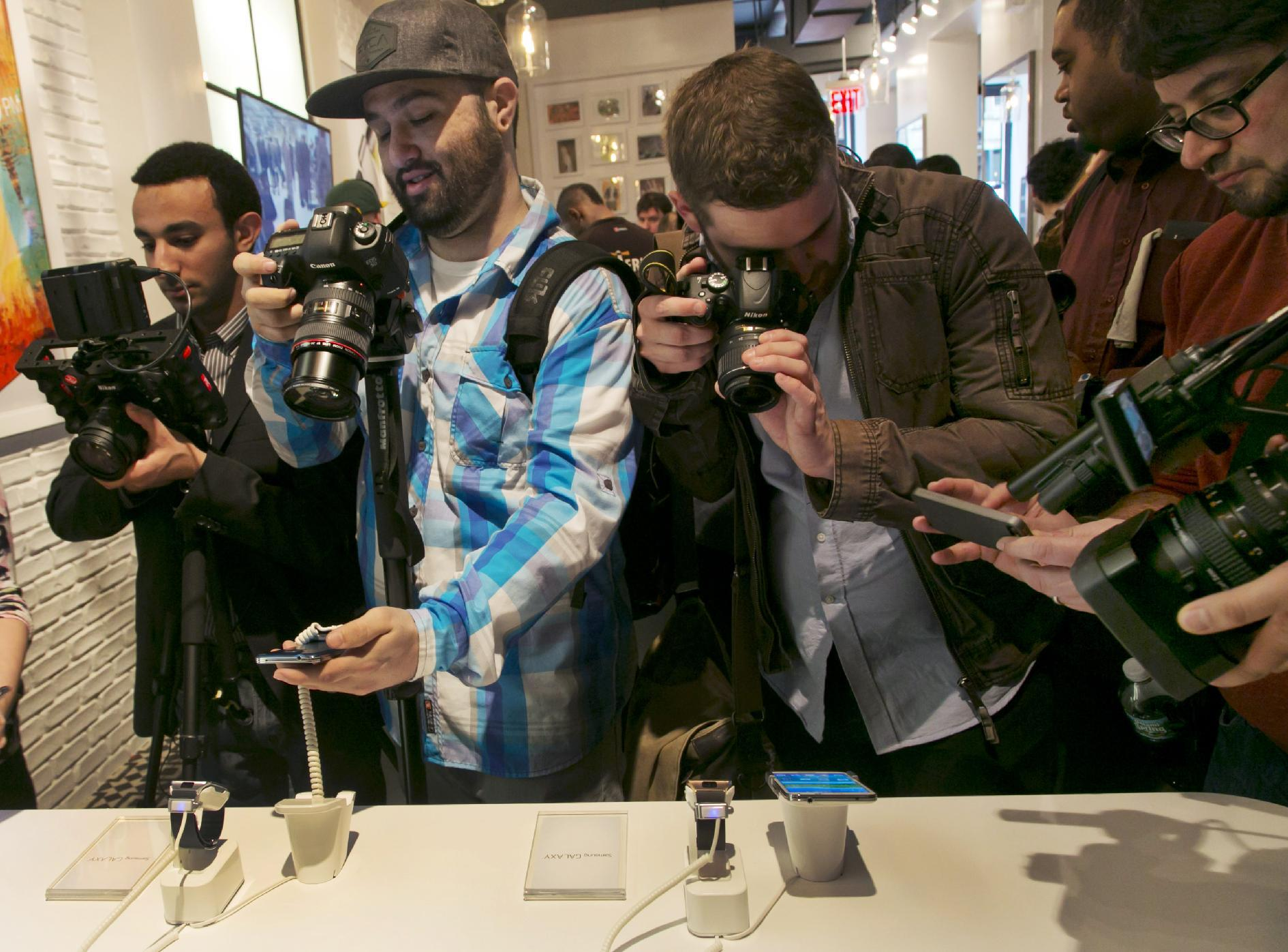 Photographers swarm around a Samsung Galaxy S5 smartphones, left, and Samsung Gear 2's at the Samsung Galaxy Studio, in New York, Monday, Feb. 24, 2014. Samsung on Monday unveiled a new smartphone with a built-in heart rate monitor to complement three upcoming fitness devices, as the Korean companies tries to turn its technological wizardry into lifestyle product. (AP Photo/Richard Drew)