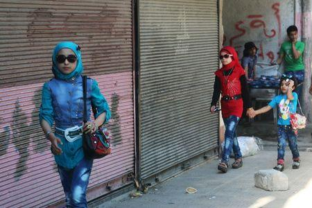 Girls walk along a street on the first day of the Muslim holiday of Eid al-Fitr, which marks the end of the holy month of Ramadan, in a rebel-held area of Aleppo