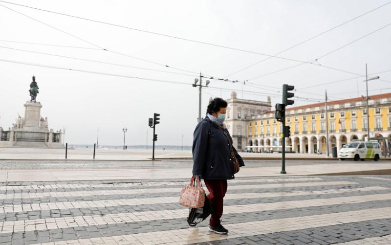A woman wearing a protective mask as a preventive measure against coronavirus disease (COVID-19) walks at Comercio Square in downtown Lisbon