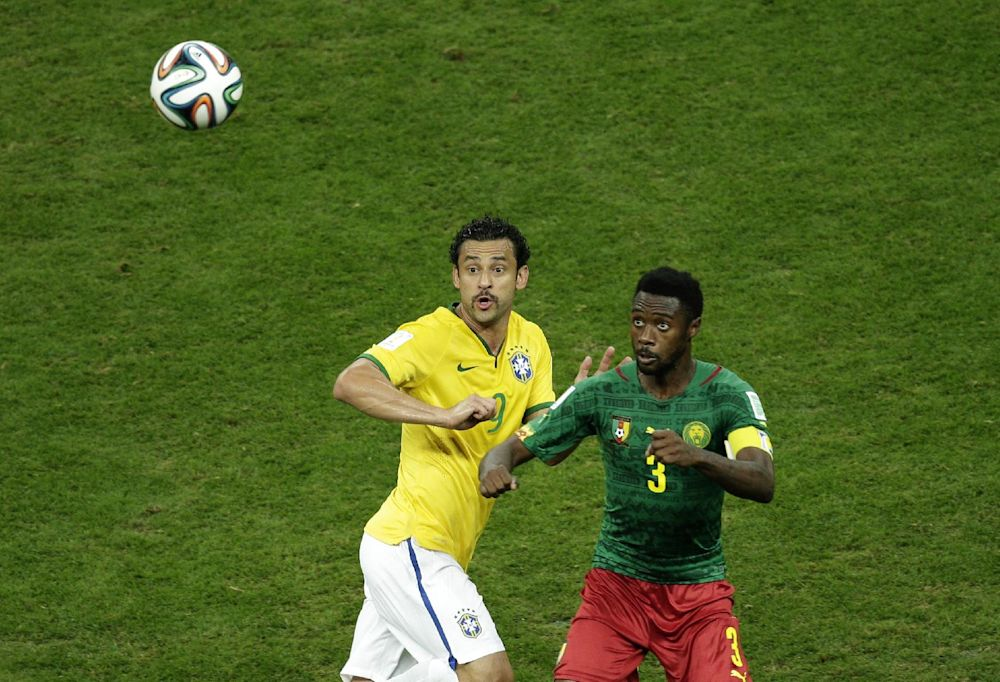 Brazil's Fred fights for the ball with Cameroon's Nicolas N'Koulou during the group A World Cup soccer match between Cameroon and Brazil at the Estadio Nacional in Brasilia, Brazil, Monday, June 23, 2014