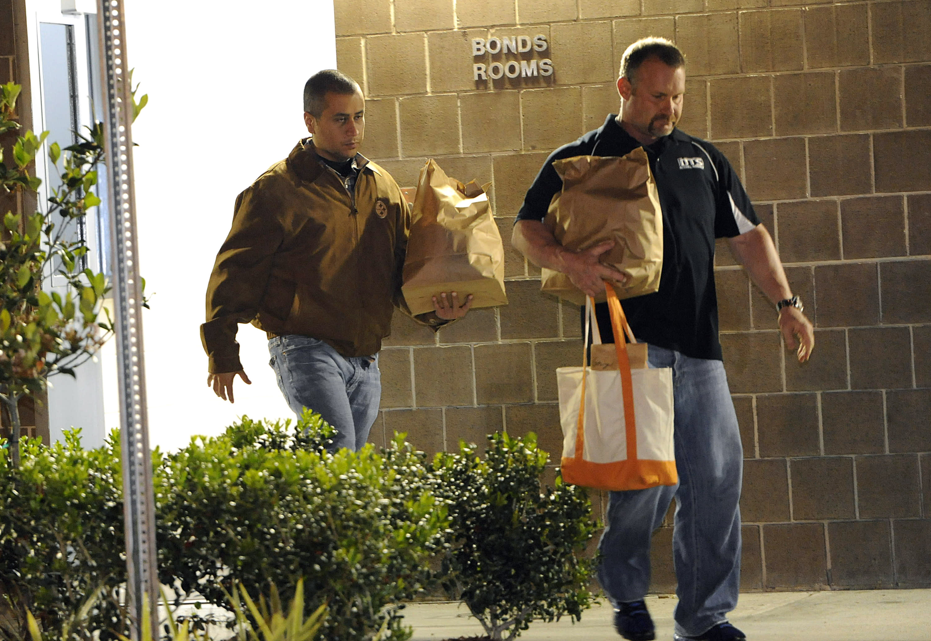 ADDS THAT THE MAN ACCOMPANYING ZIMMERMAN IS A BONDSMAN - George Zimmerman, left, walks out of the intake building at the John E. Polk Correctional Facility with a bondsman on Sunday, April 22, 2012, in Sanford, Fla. Zimmerman posted bail on a $150,000 bond on a second degree murder charge in the February shooting death of 17 year-old Trayvon Martin In Sanford, Fla. (AP Photo/Brian Blanco)