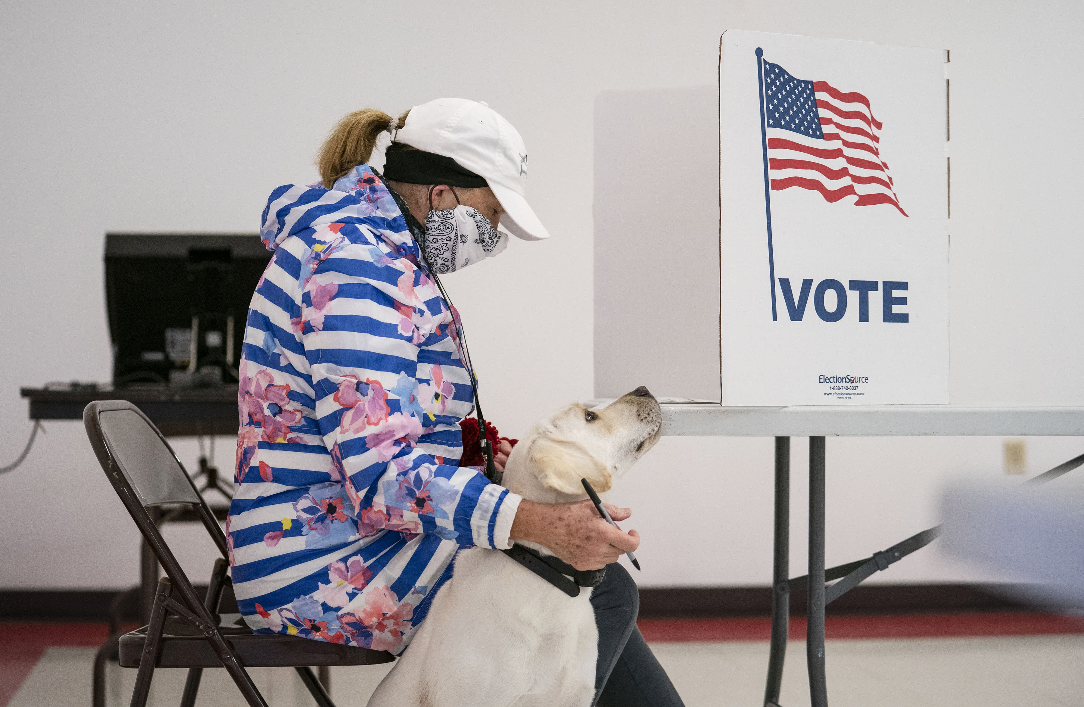 CORRECTS STATE TO WISCONSIN, NOT MINNESOTA -Catherine Anderson sits with her dog, Ivy, as she votes in the Wisconsin Primary at the Billings Park Civic Center in Superior, Wis., Tuesday, April 7, 2020. (Alex Kormann/Star Tribune via AP)