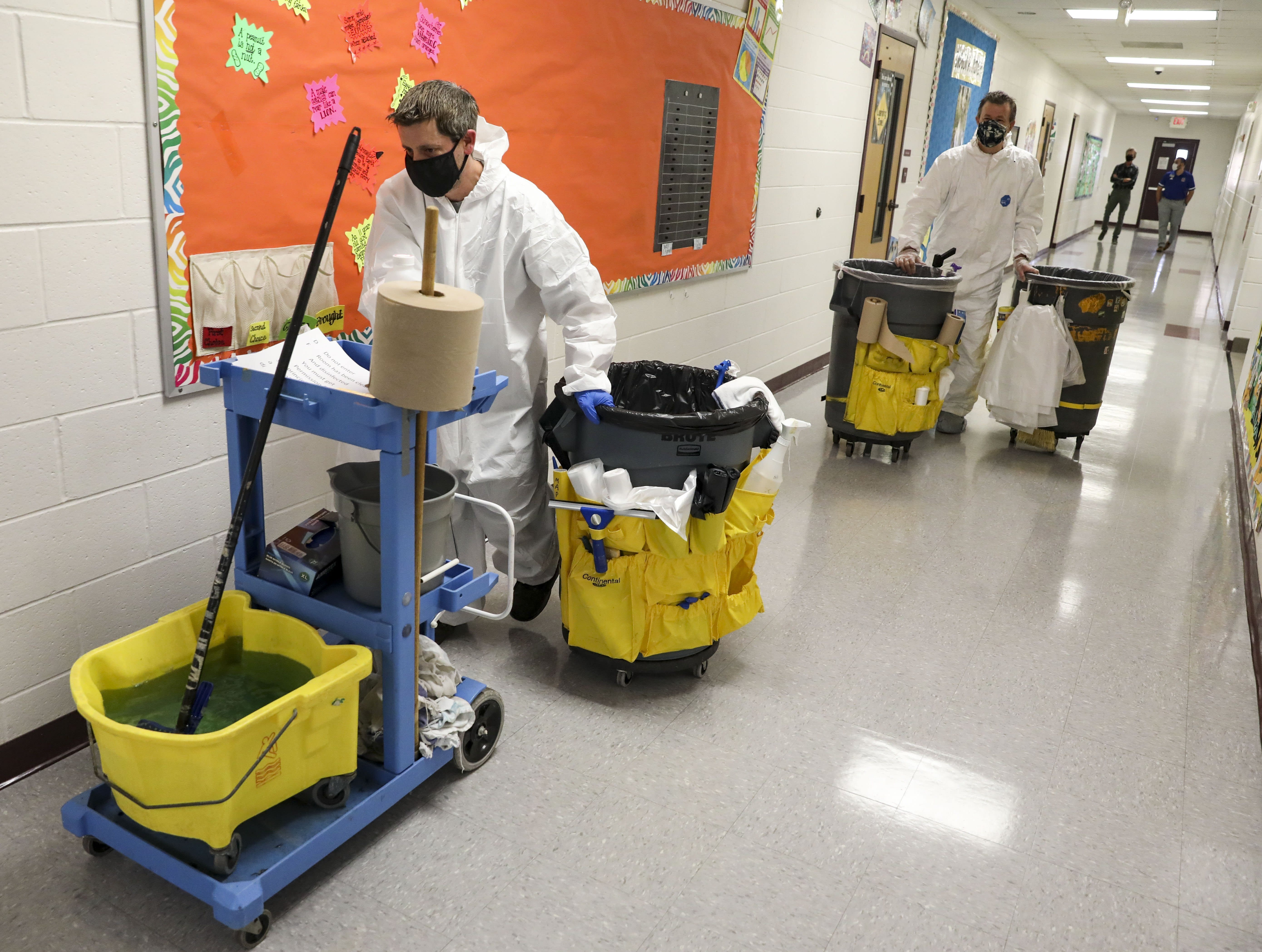 FILE - In this Nov. 5, 2020, file photo, Mike Wagner, left, and Ken Gleich, dressed in hazmat suits, wheel cleaning carts to their next classroom as they disinfect Richard A. Simpson Elementary School in Arnold, Mo. A deadly rise in COVID-19 infections is forcing state and local officials to adjust their blueprints for fighting a virus that is threatening to overwhelm health care systems. Schools are scrapping plans to reopen classrooms. More states are adopting mask mandates. (Colter Peterson/St. Louis Post-Dispatch via AP, File)