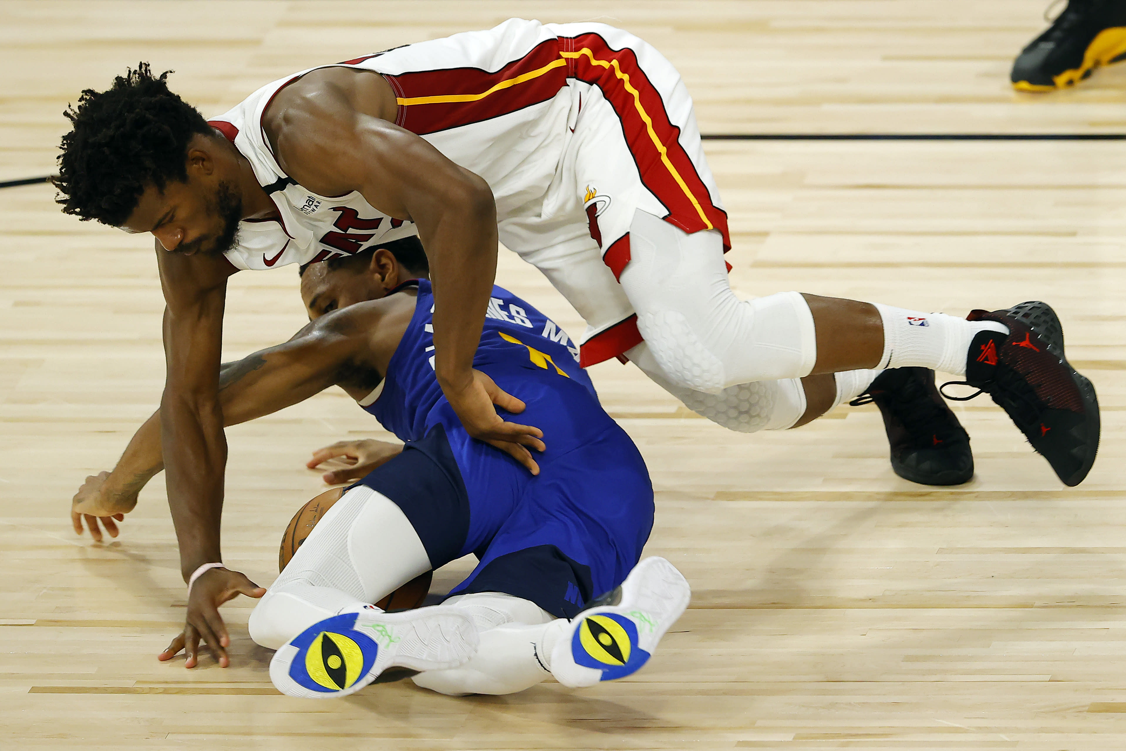 Denver Nuggets' Monte Morris, bottom, and Miami Heat's Jimmy Butler scramble for the ball during an NBA basketball game, Saturday, Aug. 1, 2020, in Lake Buena Vista, Fla. (Kevin C. Cox/Pool Photo via AP)