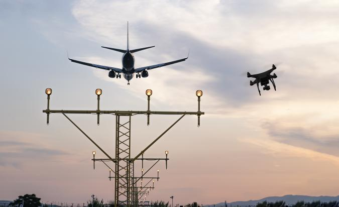 Drone flying at the airport near an aircraft leading to a possible crash or accident. Illegal UAV flight inside the airport conceptual montage