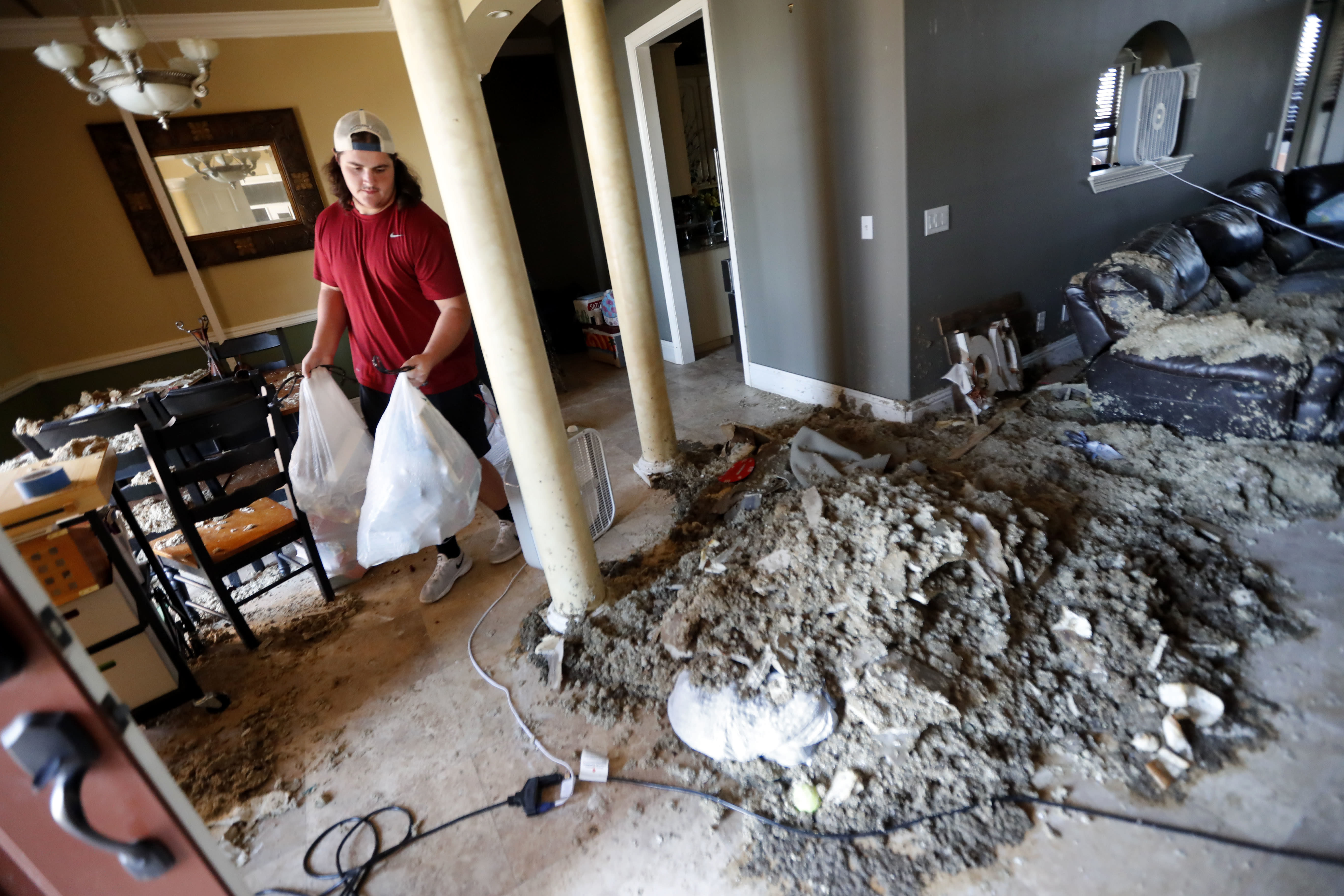 Castor Gay, who plays center for the Mosley High football team, cleans debris from his heavily damaged home, in the aftermath of Hurricane Michael in Lynn Haven, Fla., Friday, Oct. 19, 2018. (AP Photo/Gerald Herbert)